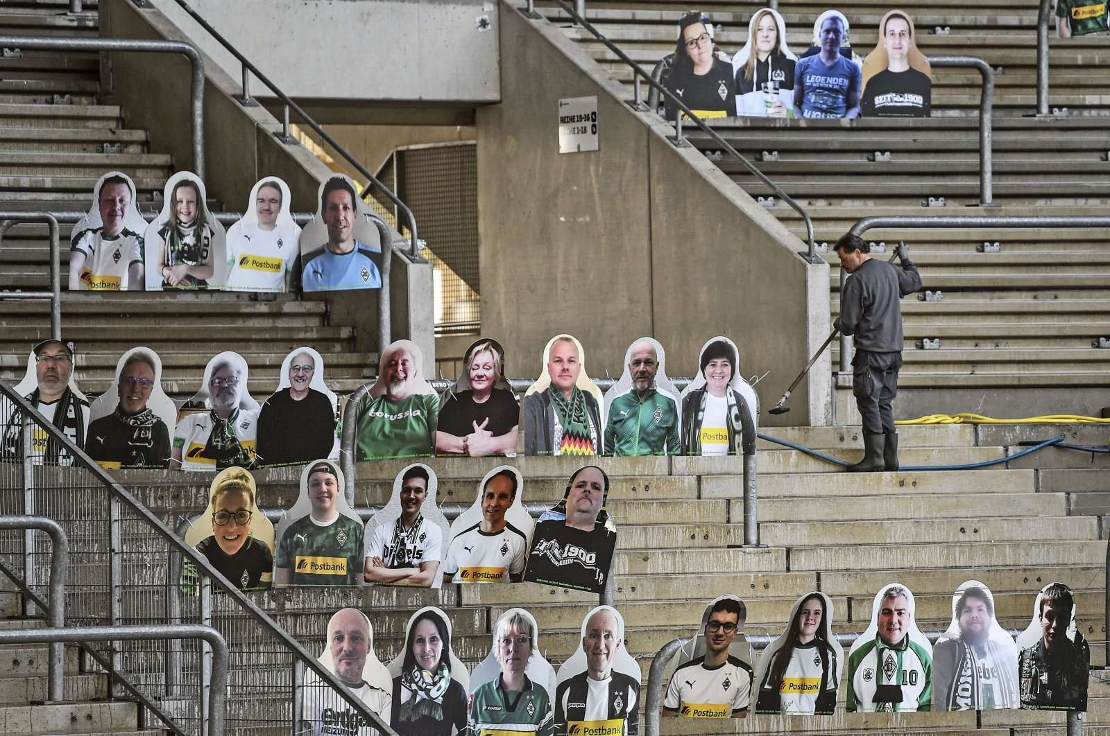 A worker cleans the supporters' tribune where portraits of fans of German Bundesliga soccer club Borussia Moenchengladbach are set in the stadium in Moenchengladbach, Germany, April 16, 2020. (AP Photo)
