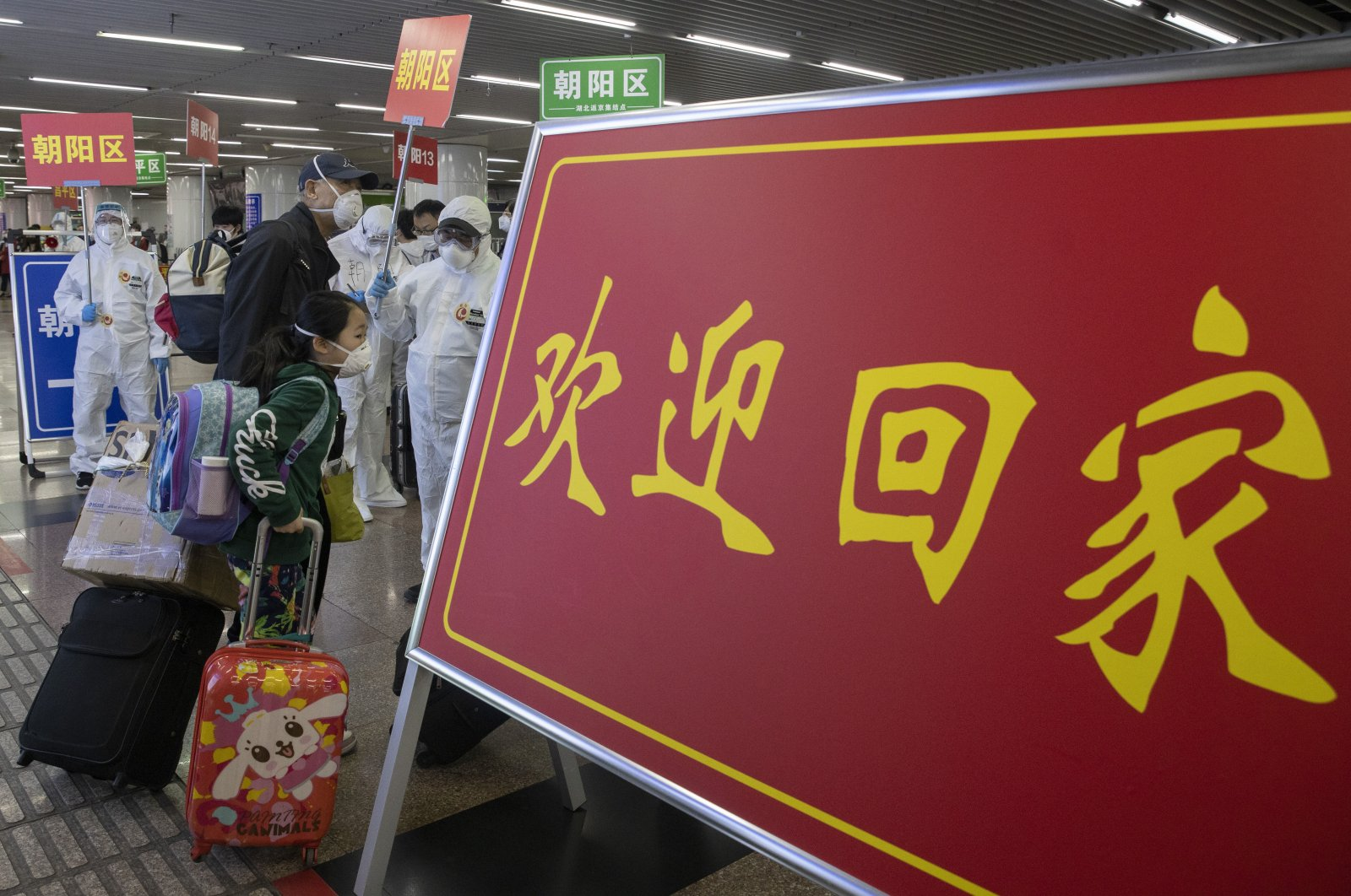"""Passengers from Wuhan walk past a sign which reads """"Welcome Home"""" after arriving on a high-speed train in Beijing, China, April 19, 2020. (AP Photo)"""