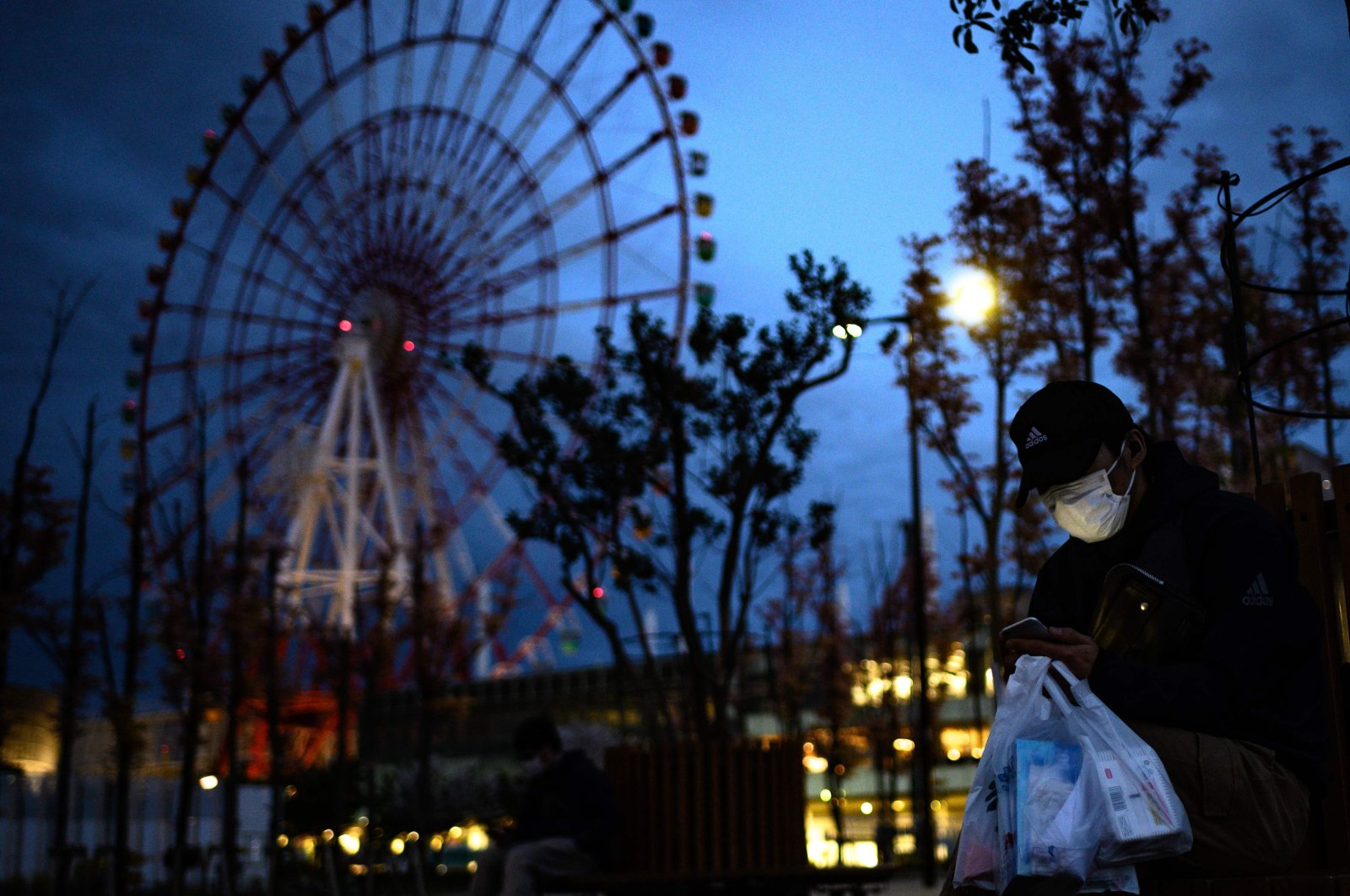 A man wearing a face mask looks at his mobile phone before a ferris wheel in the Odaiba area in Tokyo, April 19, 2020. (AFP Photo)