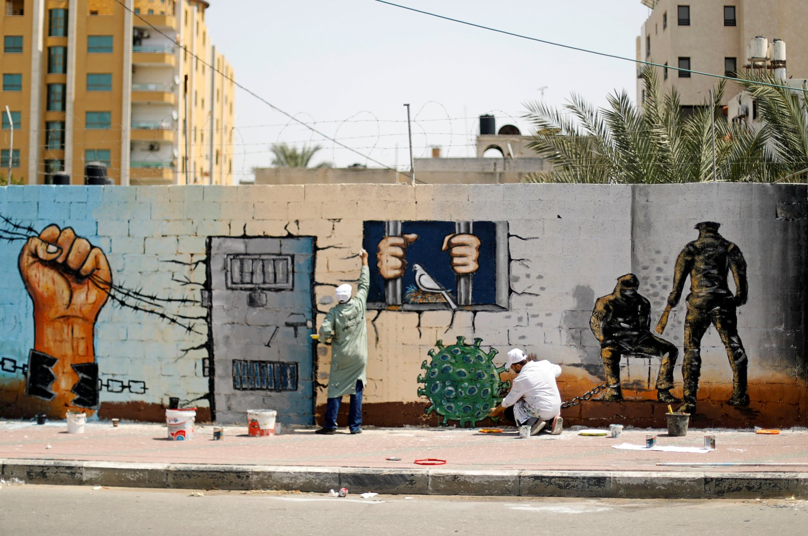 An artist paints a depiction of the microscopic view of the coronavirus chained to a prisoner as part of a mural in support of Palestinians held in Israeli jails, amid concerns about the spread of COVID-19, in Gaza City, Palestine, April 20, 2020. (Reuters Photo)