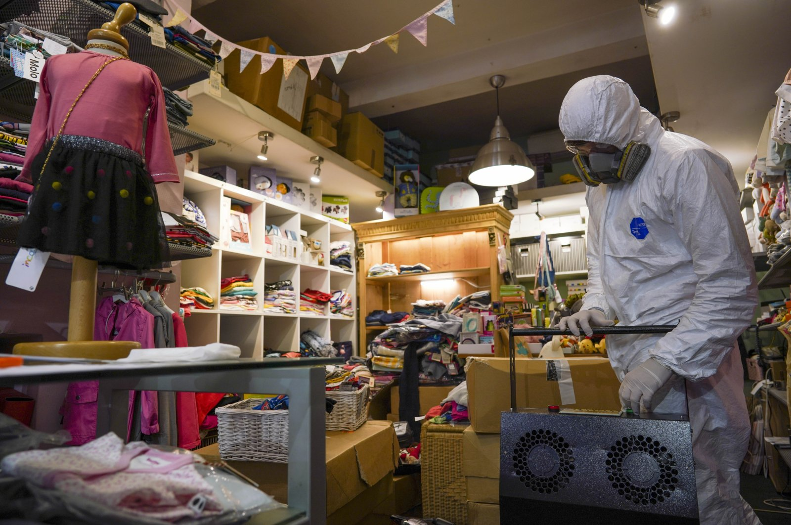 A man in protective gear prepares to sanitize a children's clothes shop before it opens to prevent the spread of COVID-19, in Rome, Italy, April 14, 2020. (AP Photo)