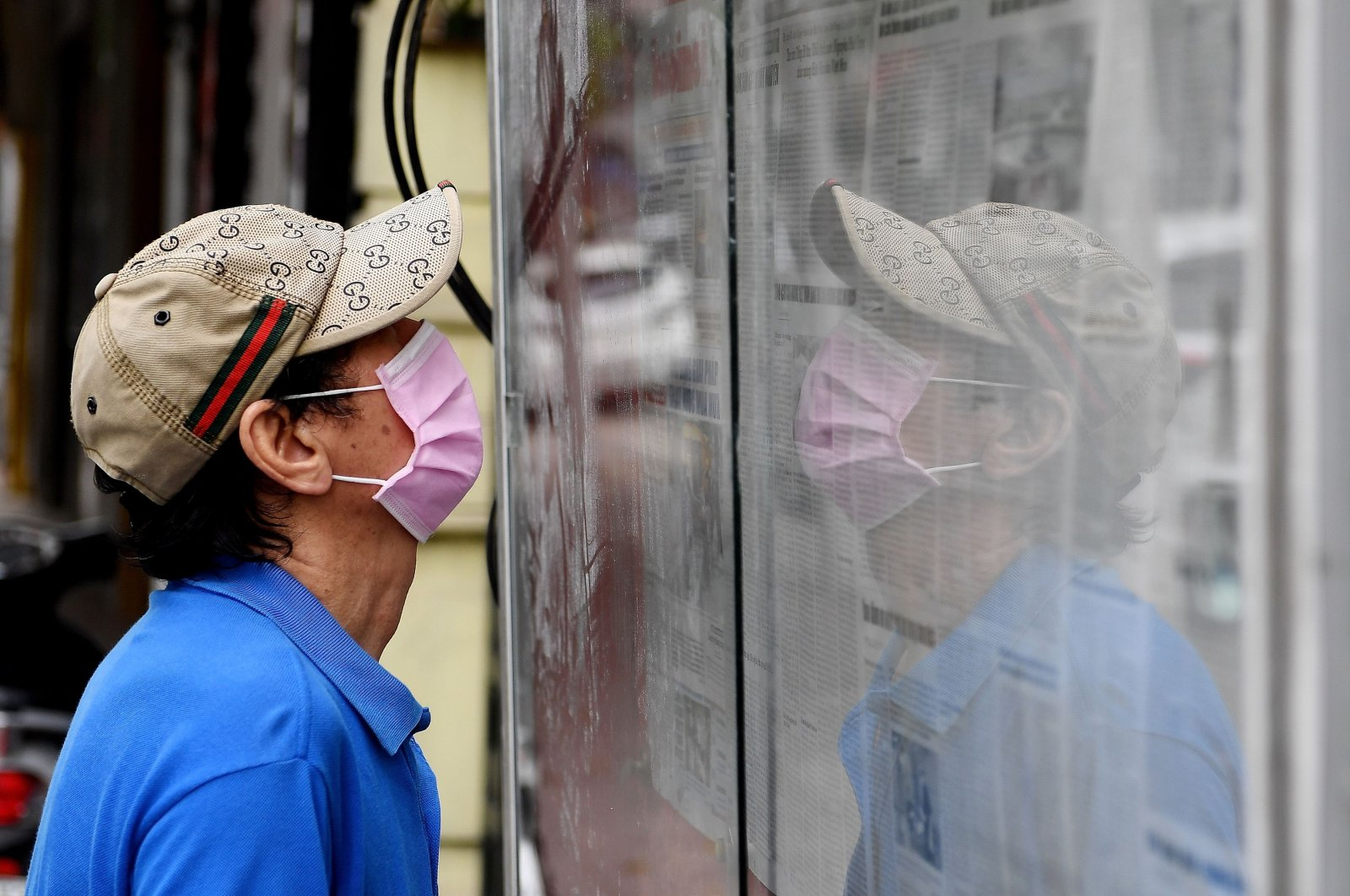 """A man wearing a face mask reads the local daily newspaper """"Hanoi Moi"""" displayed in a case on a street amid Vietnam's nationwide social isolation effort as a preventive measure against the spread of the COVID-19 coronavirus in Hanoi on April 21, 2020. (AFP Photo)"""