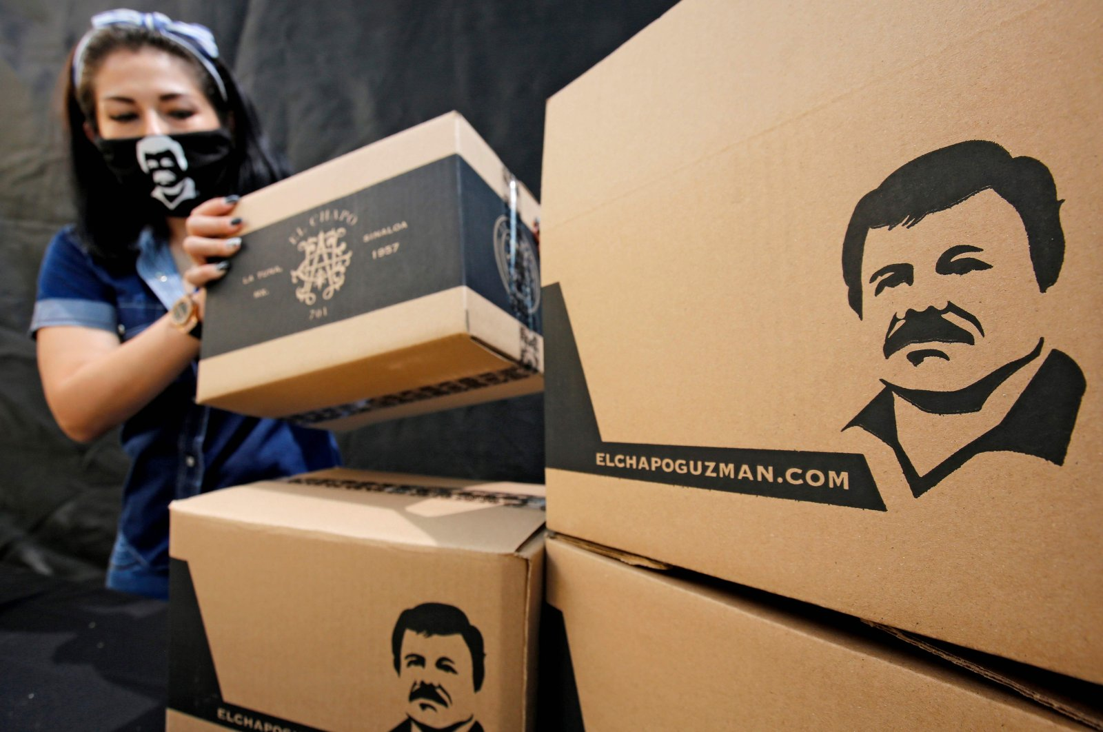 """An employee of the Alejandrina Guzman Foundation wears a face mask with the image of Mexican drug lord Joaquin """"El Chapo"""" Guzman -Alejandrina's father- as she arranges boxes with basic goods to be donated to people in need amid the new coronavirus pandemic in Guadalajara, Mexico, on April 17, 2020. (AFP Photo)"""