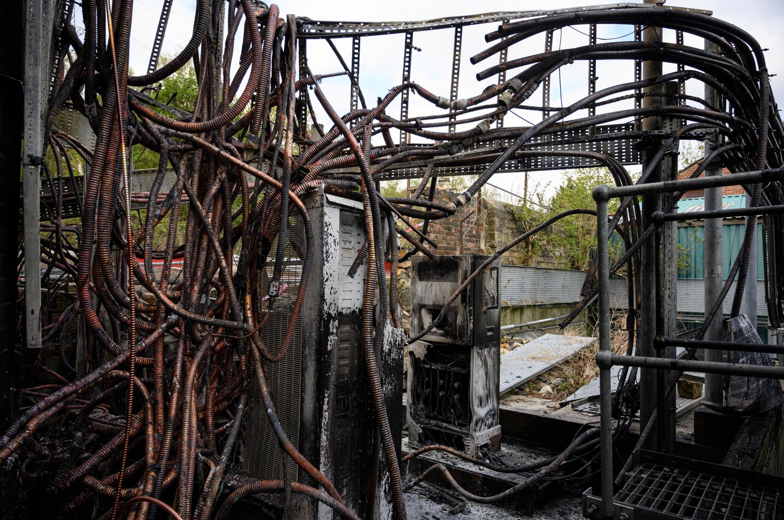 Damaged cabling and telecommunications equipment is pictured following a fire at a phone mast, attatched to the chimney at the converted Fearnleys Mill residential apartment block complex in Huddersfield, northern England, on April 17, 2020. It is not yet known what caused the mast, which is attached to a chimney at the Fearnleys Mill development, to go up in flames. But the fire comes after a number of mobile phone masts have been set on fire amid claims of a link between 5G and the novel coronavirus COVID-19. (AFP Photo)