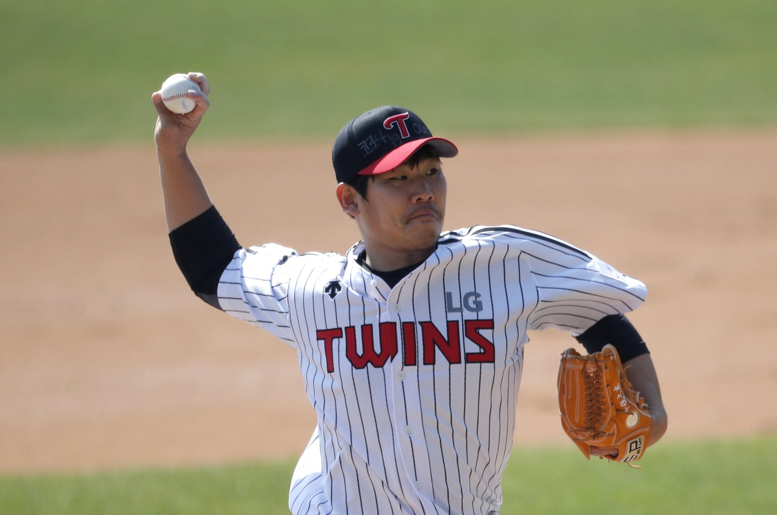 """Letters reading """"Corona 19 Out"""" is seen on the cap of LG Twins baseball team's pitcher Jeong Chan-heon as a part of campaign to overcome the coronavirus during an intrasquad baseball game in Seoul, South Korea, Sunday, April 5, 2020. (AP Photo)"""