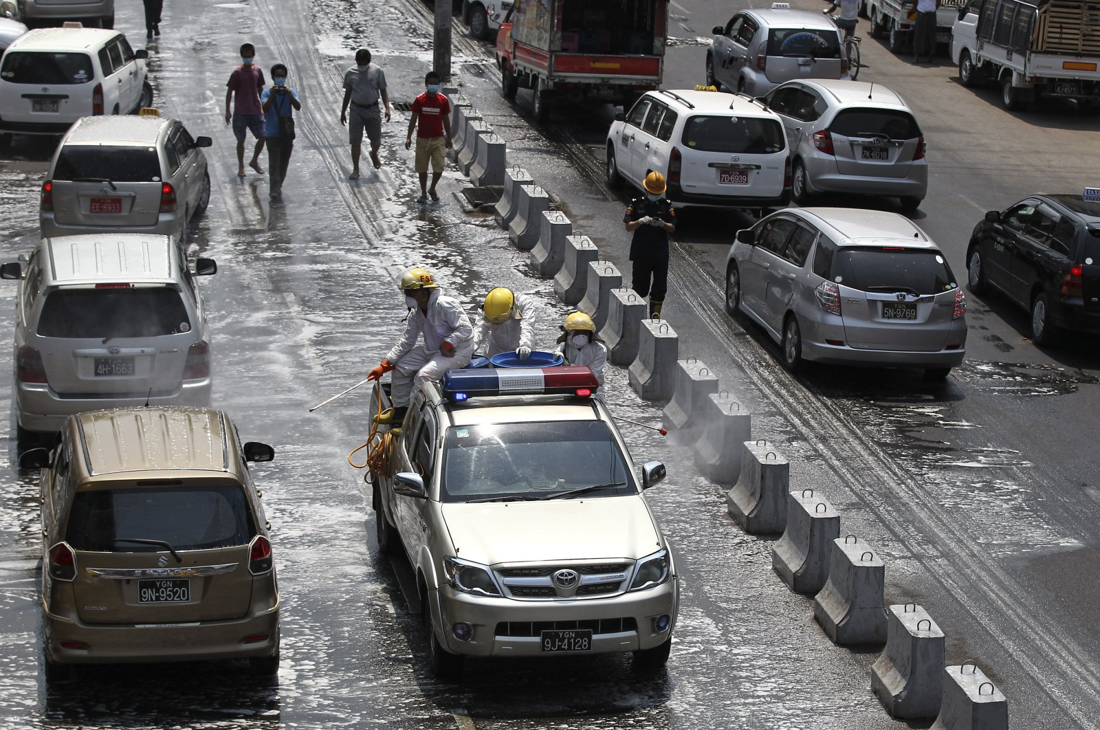 The fire department spray disinfectant to help curb the spread of the new coronavirus on a road Tuesday, April 21, 2020, in Yangon, Myanmar. (AP Photo)