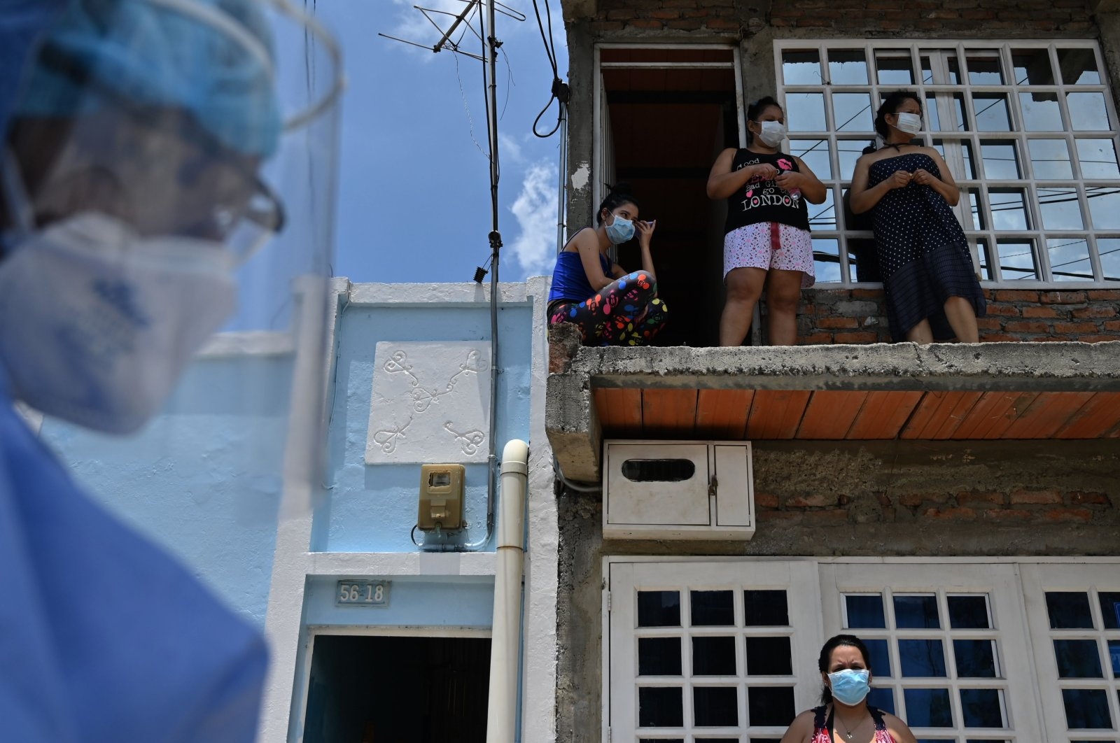 Locals look out from their house as health workers wearing biosafety suits carry out a checkup for the coronavirus at Nueva Floresta neighborhood in Cali, Colombia, on April 20, 2020.  (AFP)