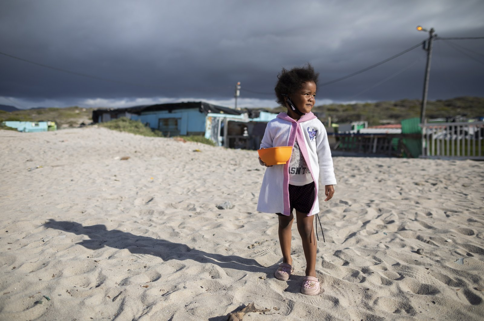 A girl from the 7de Laan shack settlement waits for food from the 9 Miles Project COVID-19 community support program in Strandfontein, Cape Town, South Africa, April 20, 2020. (EPA Photo)