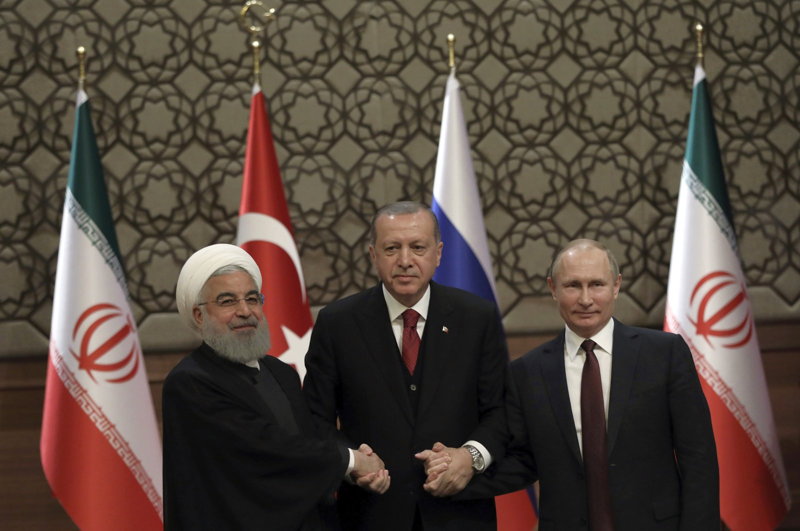 Iranian President Hassan Rouhani (L), Turkish President Recep Tayyip Erdogan (C) and Russian President Vladimir Putin (R) join hands after a joint news conference in Ankara, Turkey, April 4, 2018. (AP Photo)