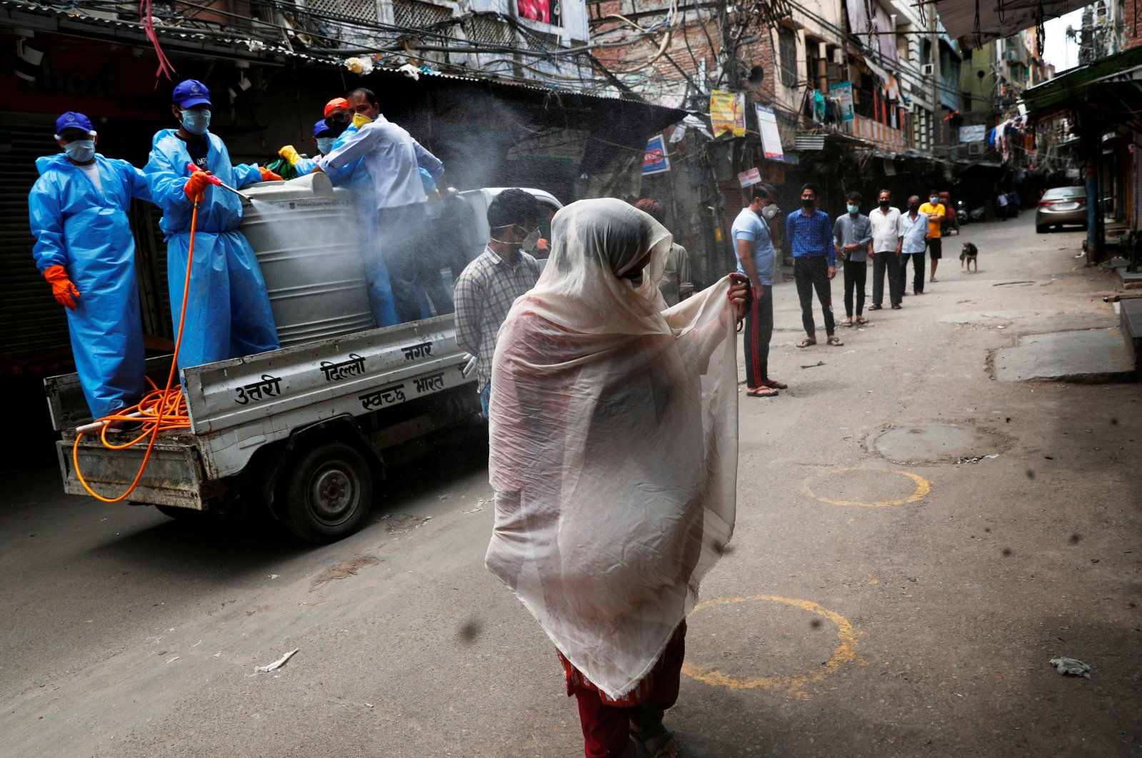 Municipal workers spray disinfectant on the people stand in a queue next to a mobile test station for coronavirus disease (COVID-19) at a residential area in the old quarters of Delhi, India, April 20, 2020. (Reuters Photo)