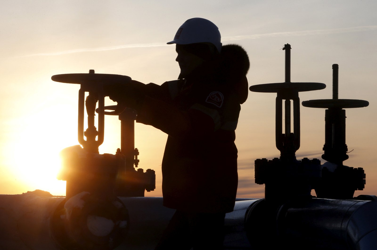 A worker checks the valve of an oil pipe at the Lukoil company owned Imilorskoye oil field outside the West Siberian city of Kogalym, Russia, January 25, 2016. (REUTERS Photo)