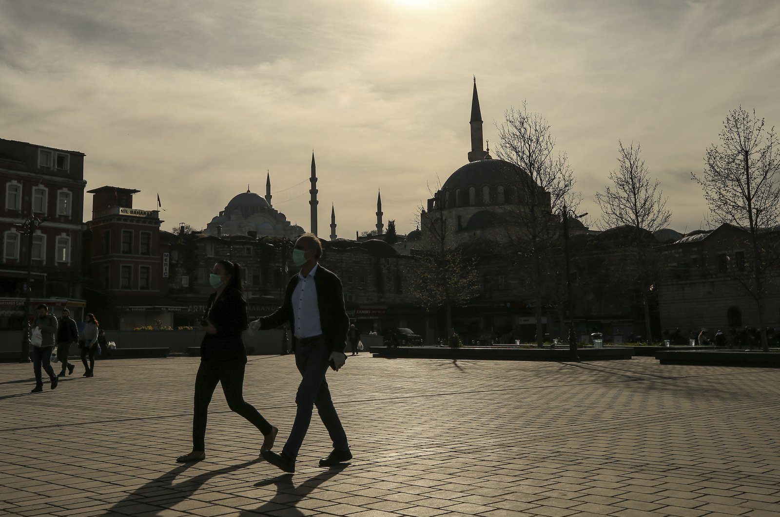 People wearing masks walk in the Eminönü neighborhood with iconic Süleymaniye Mosque in the backdrop, Istanbul, Turkey, April 17, 2020. (AP Photo)