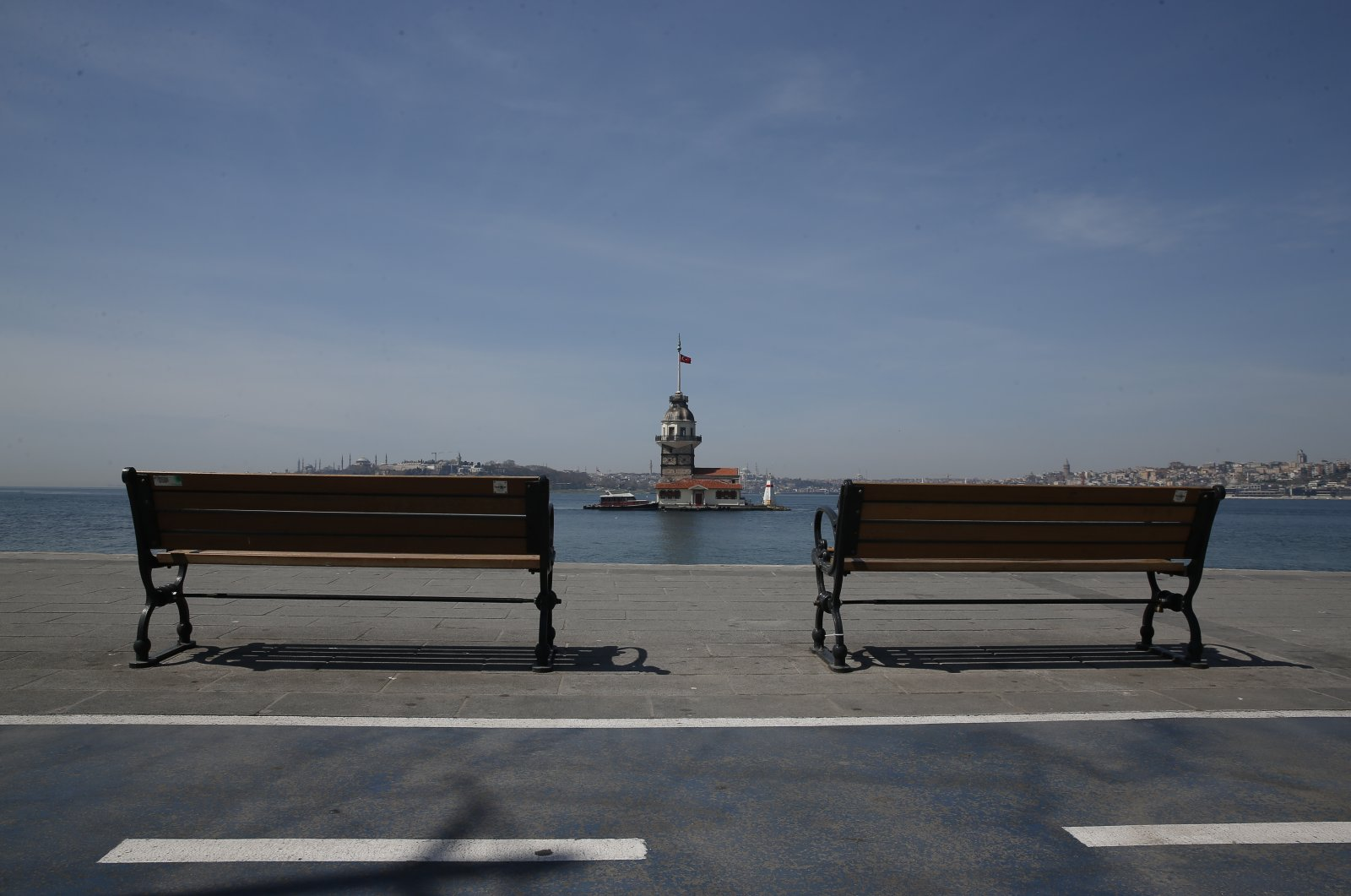 Istanbul's iconic Maiden's Tower flanked by empty benches by the Bosporus Strait, April 19, 2020. (AP Photo)