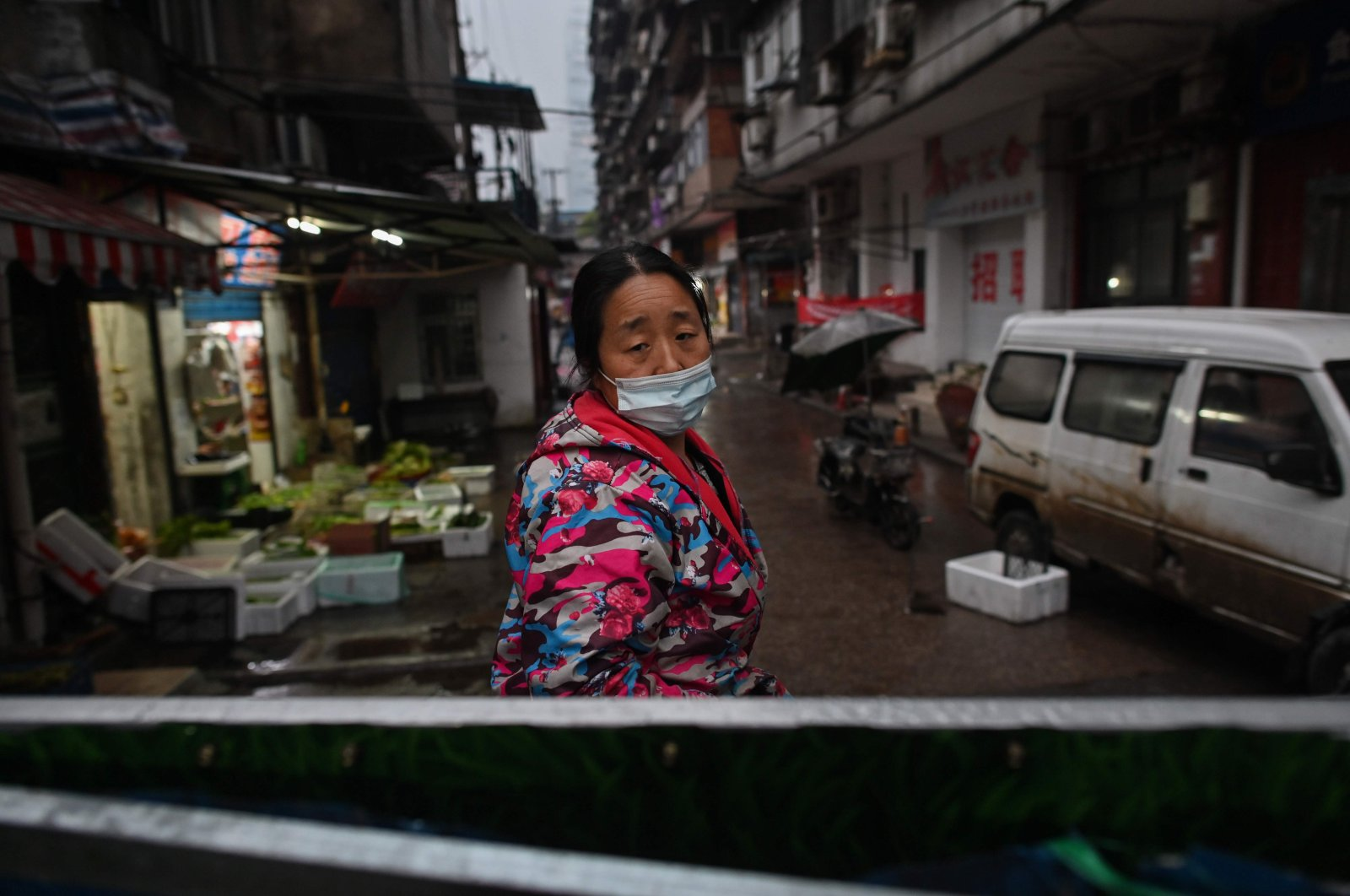 A woman, wearing a face mask as a preventive measure against the spread of the COVID-19 stands at an access to a neighborhood closed off by barriers in Wuhan, China's central Hubei province, Monday, April 20, 2020. (AFP Photo)
