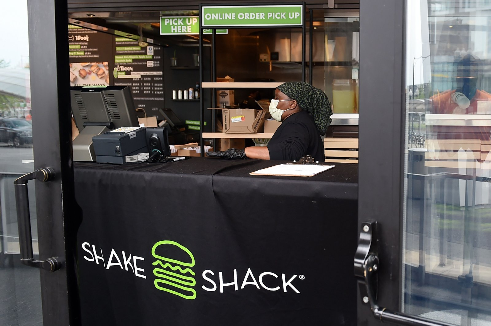 A Shake Shack employee wears a masks as she prepares food orders for pickup during the coronavirus pandemic, in Arlington, Virginia, U.S., April 20, 2020. (AFP Photo)