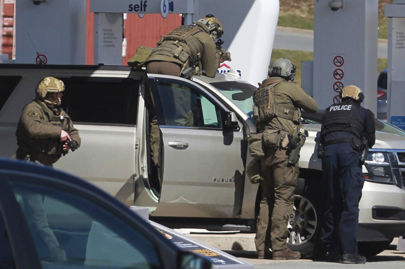 In this April 19, 2020, file photo, Royal Canadian Mounted Police officers surround a suspect at a gas station in Enfield, Nova Scotia. Canadian police say multiple people are dead plus the suspect after a shooting rampage across the province of Nova Scotia. (Tim Krochak/The Canadian Press via AP)