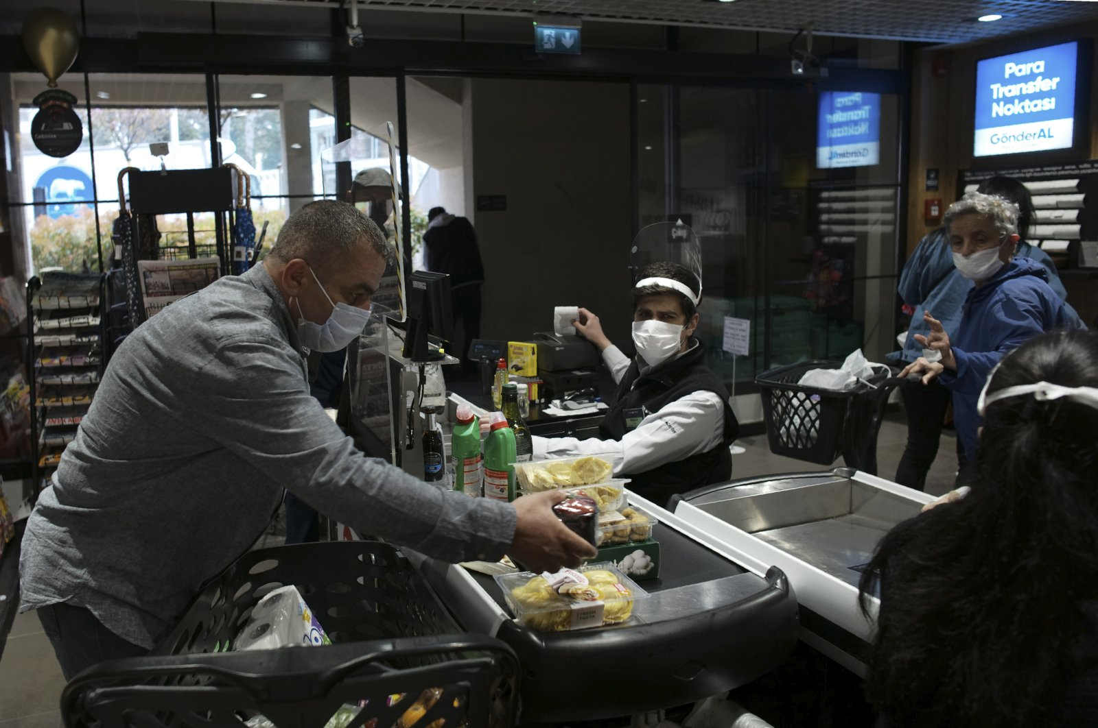 People wearing face masks shop for food at a market, in Ankara Turkey, Tuesday, April 21, 2020, two days before the start of a four-day curfew declared by the government in an attempt to control the spread of coronavirus. (AP Photo)