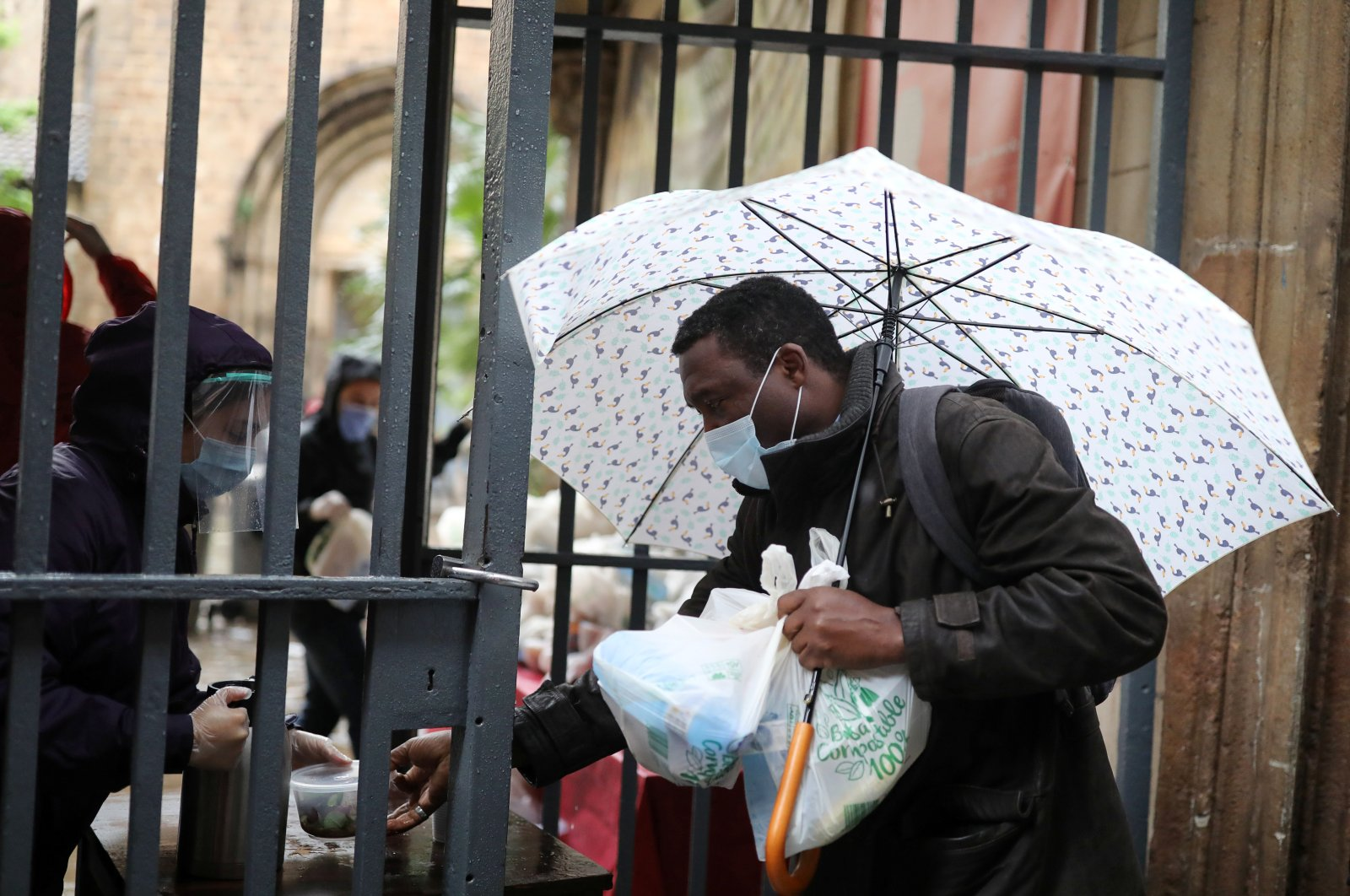 Volunteers give free food packages for a man amid economic hardship outside parish church of Santa Anna, amid the spread of the coronavirus disease (COVID-19), in Barcelona, Spain, April 21, 2020. (Reuters Photo)
