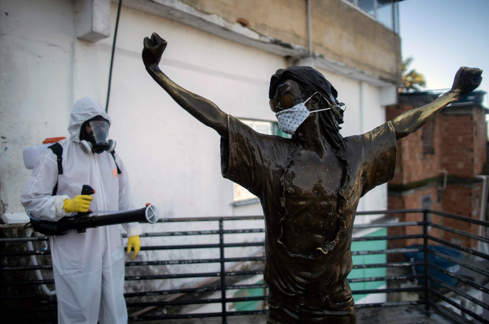 A volunteer disinfects the statue of US singer Michael Jackson, at the Santa Marta favela in Rio de Janeiro, Brazil, during the COVID-19 coronavirus pandemic on April 20, 2020. (AFP Photo)