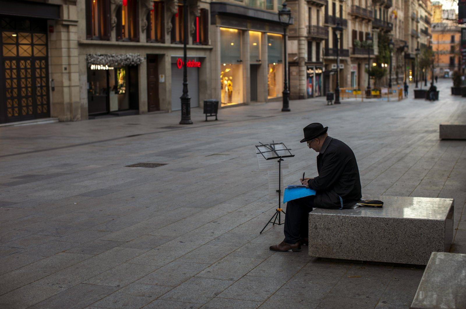 A man sits in an empty street in Barcelona, Spain, March 15, 2020. (AP Photo)