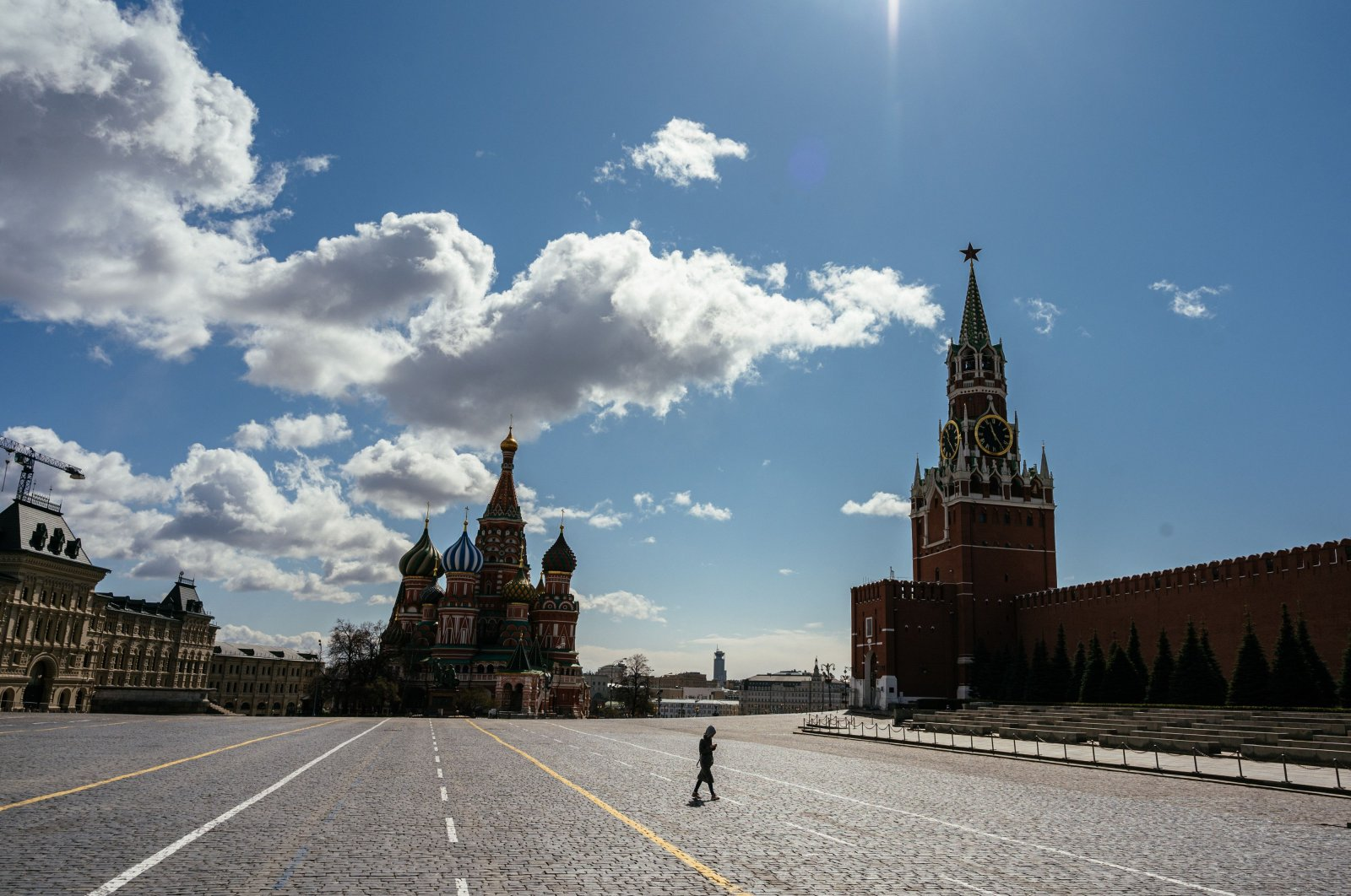 A person walks on the deserted Red Square in front of St. Basil's Cathedral and the Kremlin's Spasskaya Tower in downtown Moscow on April 22, 2020, during a strict lockdown in Russia to stop the spread of the novel coronavirus COVID-19. (AFP Photo)