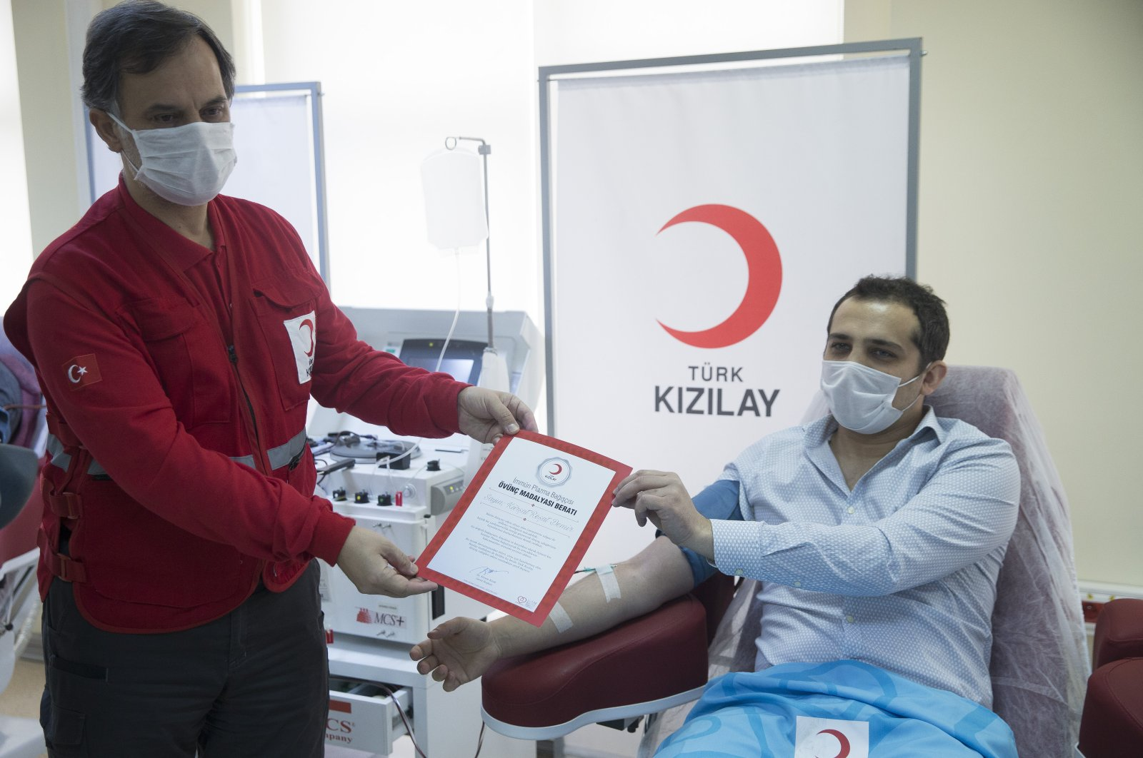Dr. Kürşat Reşat Demir receives his medal from İbrahim Altan, general director of the Turkish Red Crescent, in Ankara, April 21, 2020. (AA Photo)