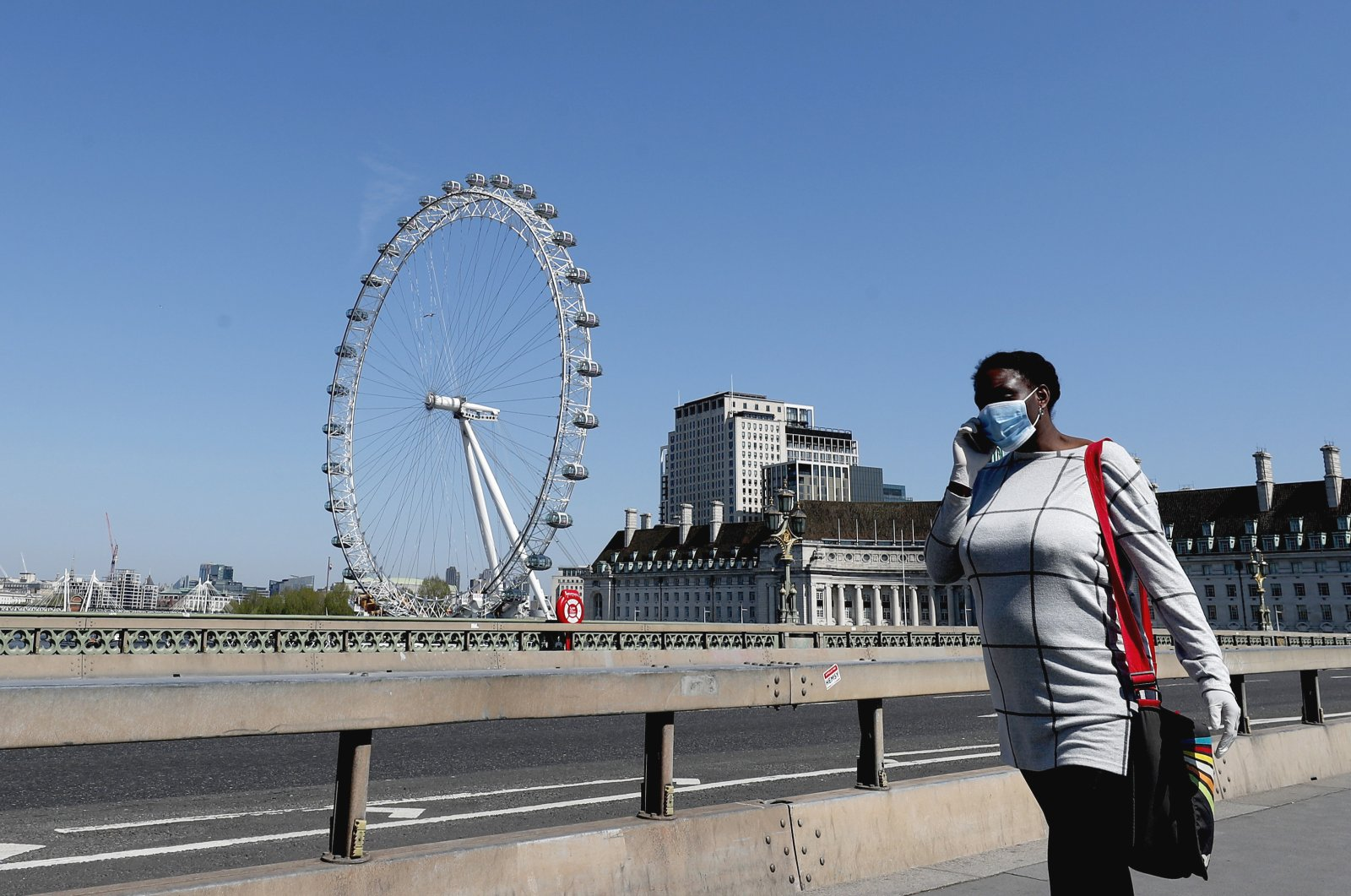 A woman wearing a protective mask walks over Westminster Bridge in London, England, April 22, 2020. (AP Photo)
