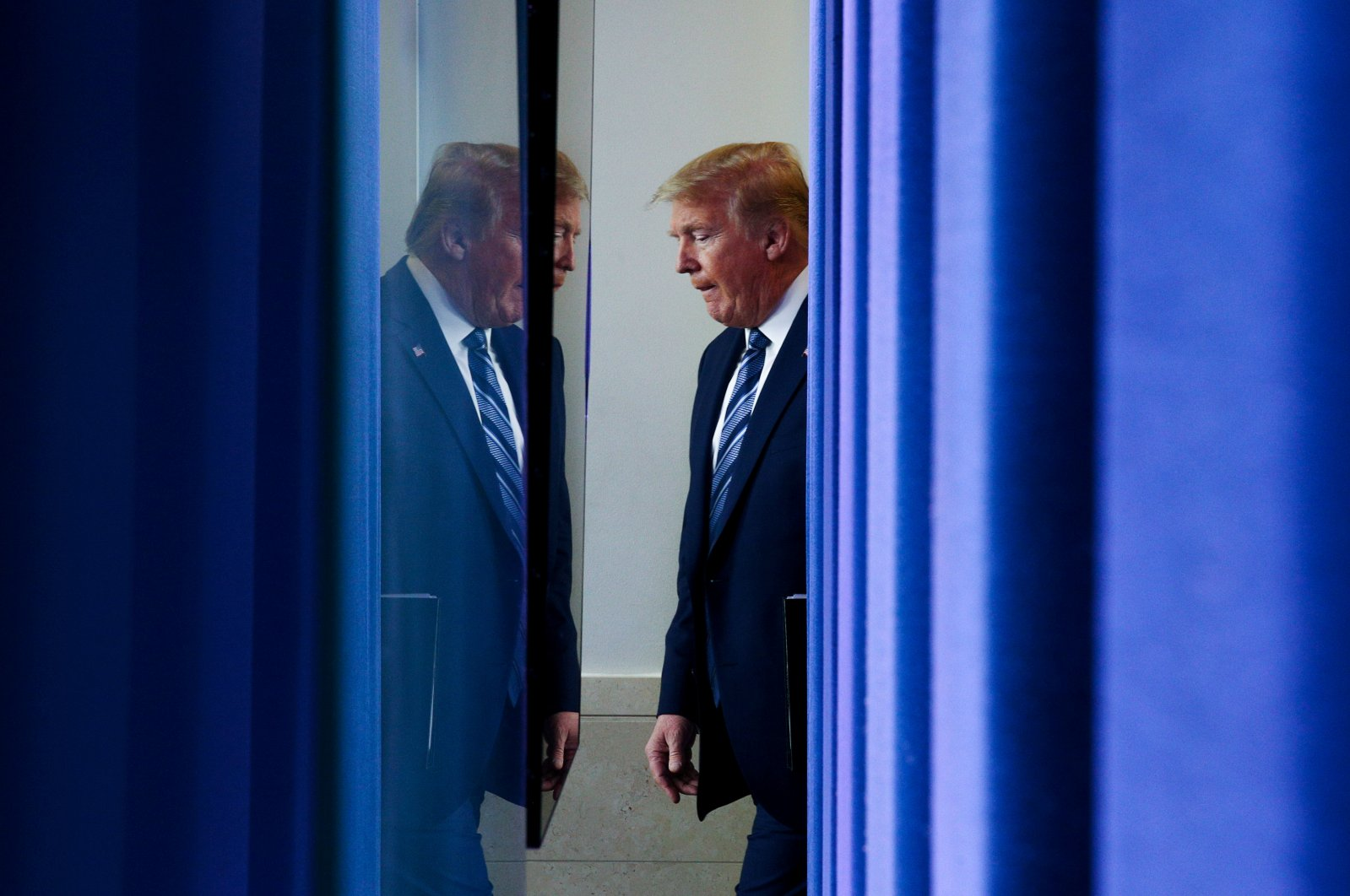 U.S. President Donald Trump arrives to lead the daily coronavirus task force briefing as seen from behind the backdrop of the Brady press briefing room at the White House in Washington, U.S., April 21, 2020. (Reuters Photo)