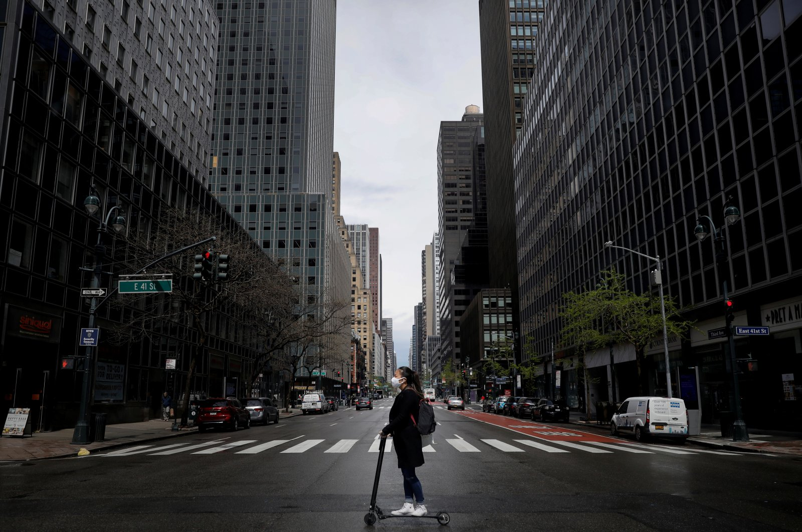 A woman wearing a protective face mask rides a scooter across a nearly empty 3rd Avenue in midtown Manhattan during the coronavirus outbreak, in New York City, New York, U.S., April 21, 2020. (Reuters Photo)