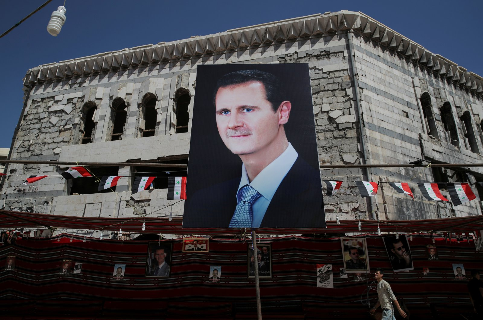 A man walks past a banner depicting Syria's Bashar Assad in Douma, outside Damascus, Syria, Sept. 17, 2018. (Reuters Photo)