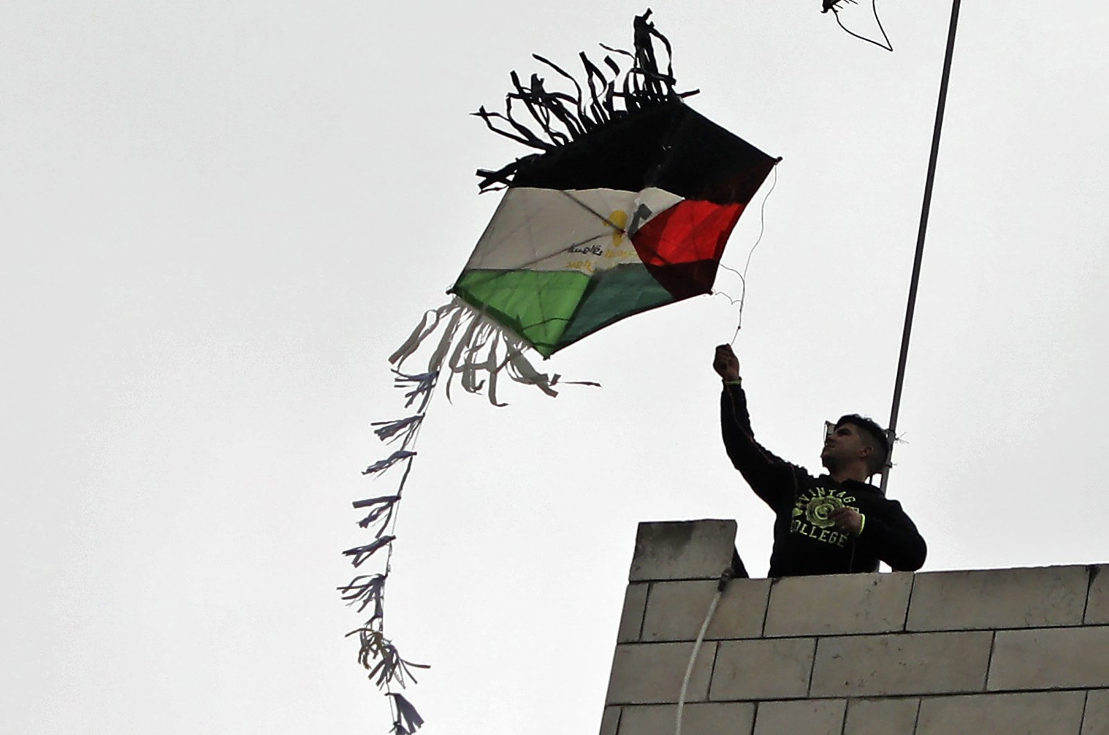 A Palestinian youth flies a kite designed as a national flag from his home during confinement due to the COVID-19 pandemic, in the West Bank city of Nablus, Palestine, April 17, 2020. (AFP Photo)