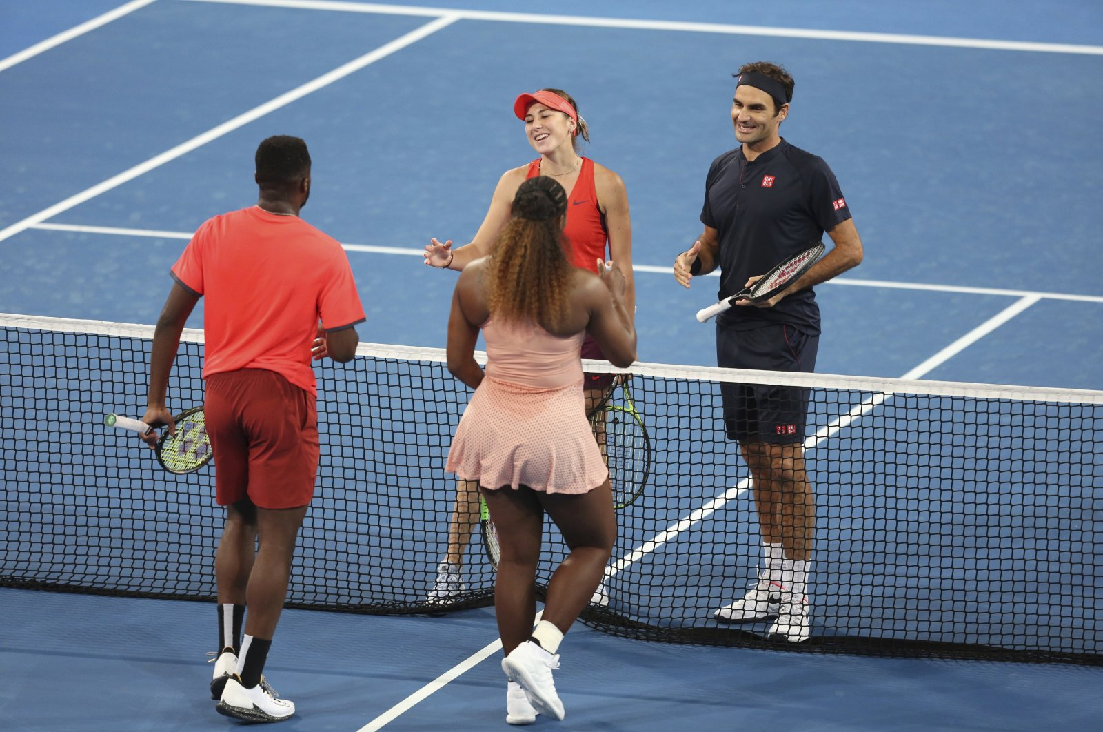 Roger Federer and Belinda Bencic wait at the net after winning their mixed doubles match against Frances Tiafoe and Serena Williams the Hopman Cup in Perth, Australia, Jan. 1, 2019. (AP Photo)