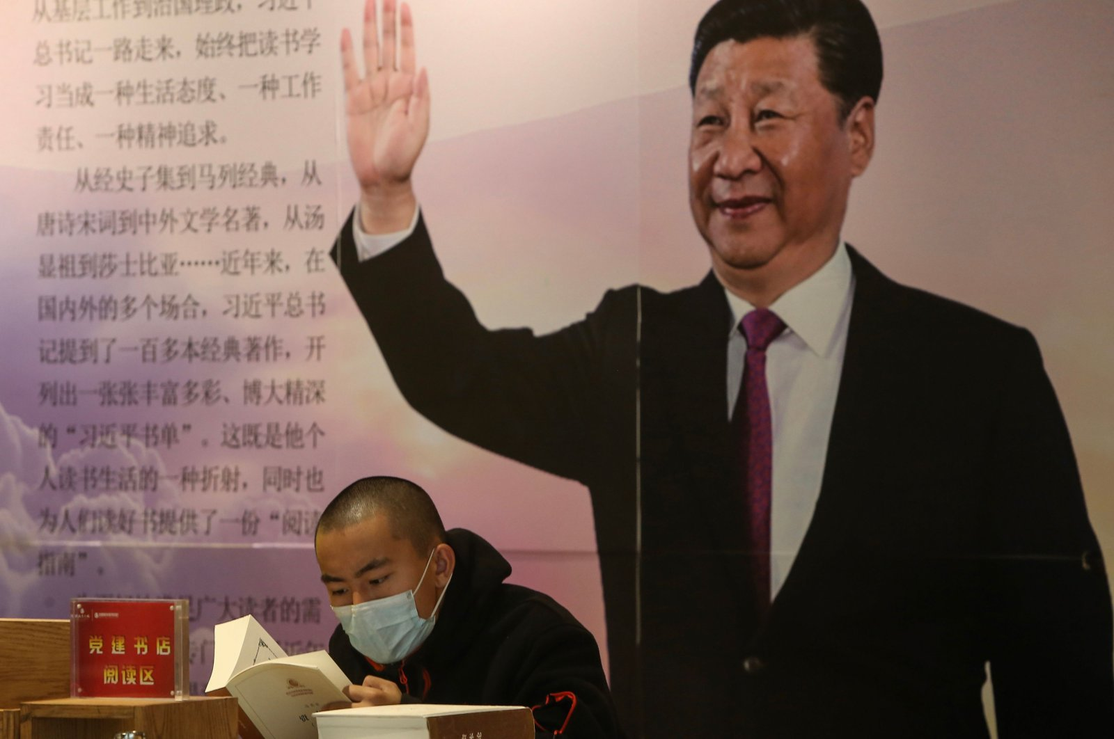 A man reads a book in front of a board with an image of China's President Xi Jinping at a book store during World Book Day in Shenyang in China's northeastern Liaoning province on April 23, 2020. (AFP Photo)