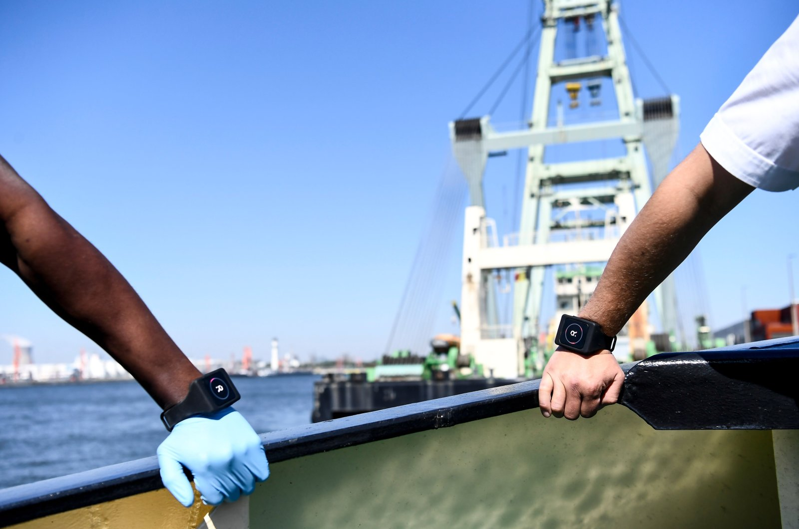 A Belgian deckhand and a captain wear Romware Covid Radius bracelets during a presentation of the device at the Port of Antwerp, on April 22, 2020. (AFP Photo)
