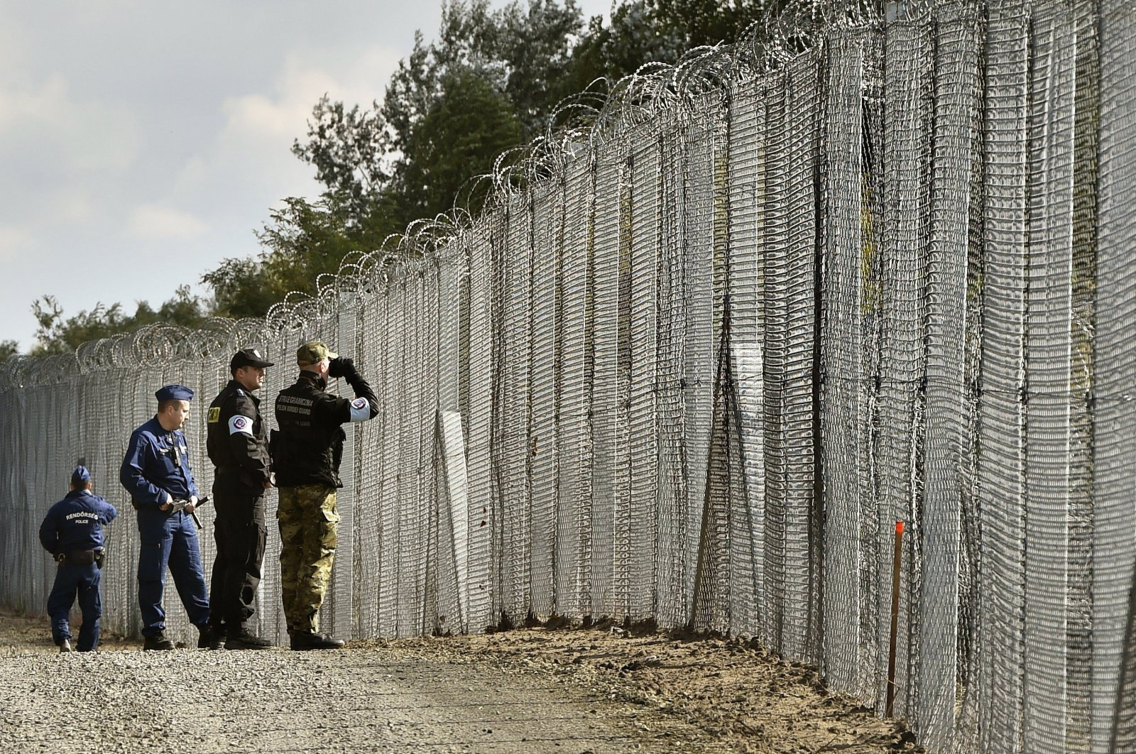 A police officer, second right, and border guard, right, of Poland patrol with Hungarian policemen along the temporary border fence on the Hungarian-Serbian border near Roszke, 180 kms southeast of Budapest, Oct. 13, 2016. (AP Photo)