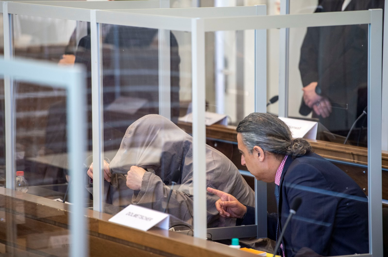 Syrian defendant Eyad A. hides himself under his hood prior to the first trial of suspected members of Syrian regime's security services for crimes against humanity, in Koblenz, Germany, April 23, 2020. REUTERS