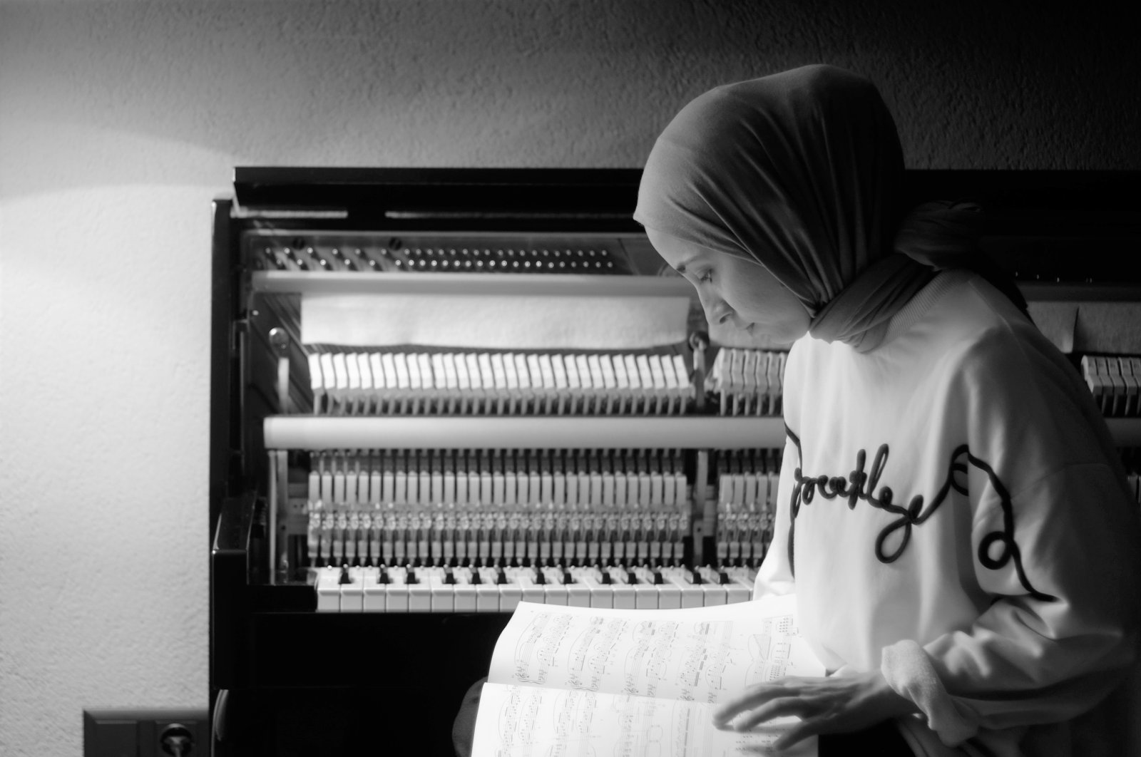Büşra Kayıkçı poses with a music notebook in front of her piano. (Courtesy of Büşra Kayıkçı)
