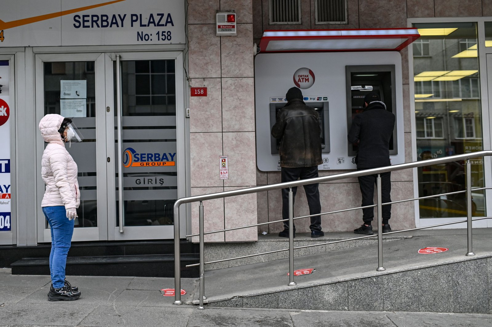 People queue to use ATM machines while observing social distancing rules outside a bank in Istanbul, Turkey, April 21, 2020. (AP Photo)
