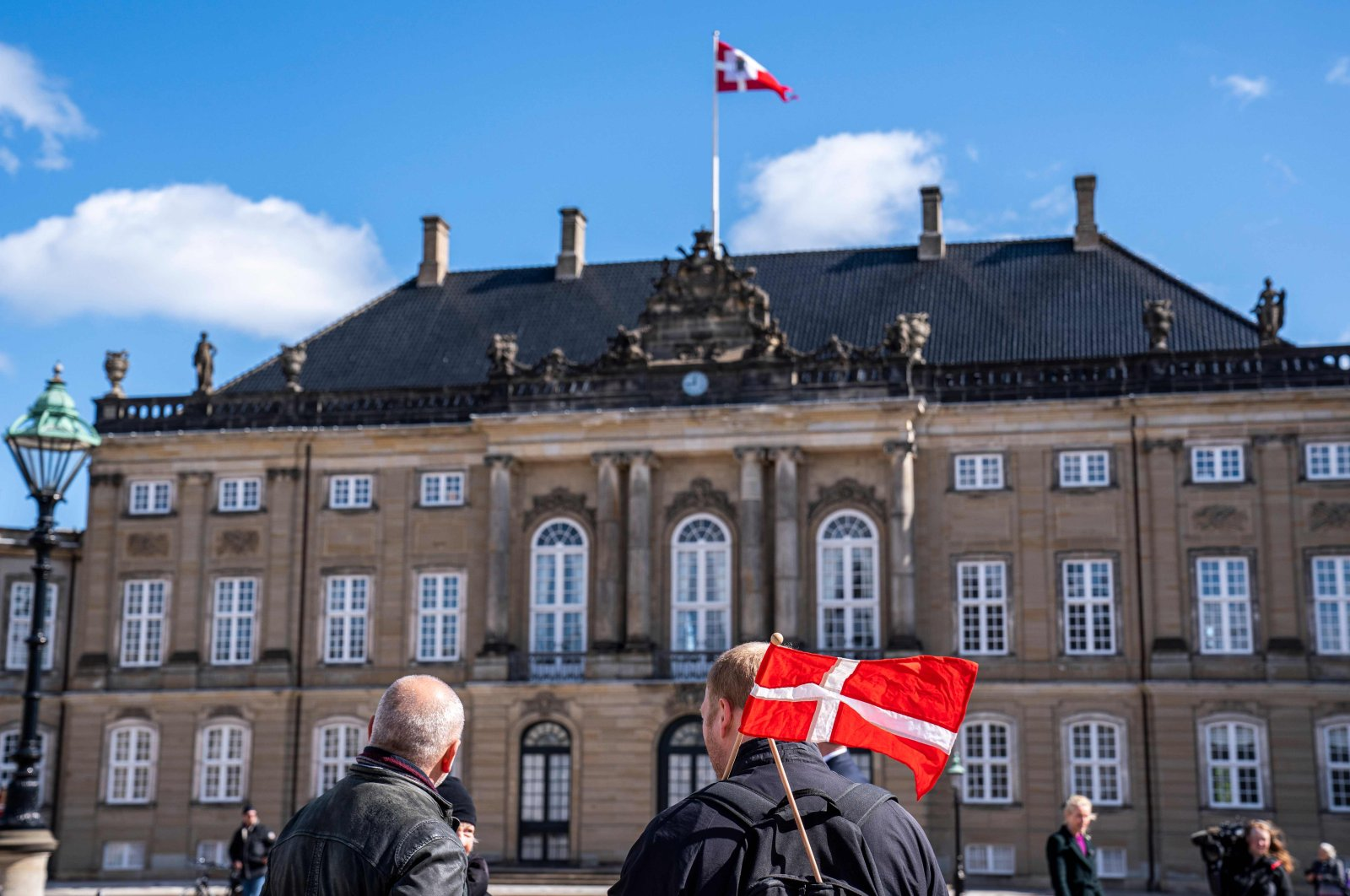 People are seen at Amalienborg Palace Square to mark the birthday of Danish Queen Margrethe in Copenhagen on April 16, 2020. (AFP Photo)