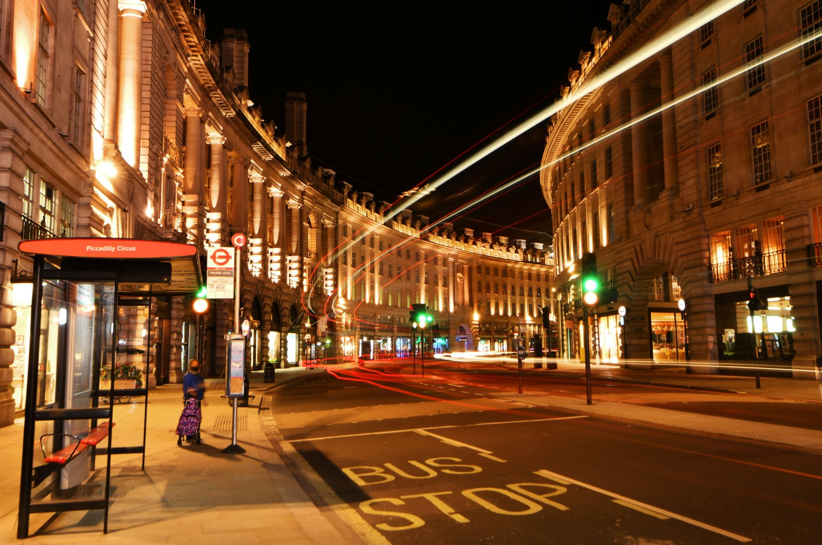 A woman waits for a bus on a quiet Regents Street during the late evening, as the city at night is deserted like never before while the coronavirus disease (COVID-19) lockdown continues, in London, Britain April 21, 2020. (Reuters Photo)