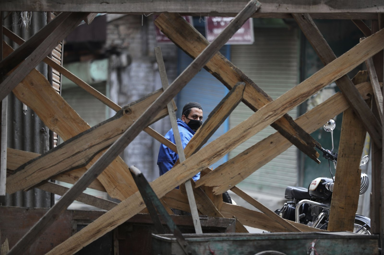 A Kashmiri volunteer looks through temporary barricades erected to prevent outsiders from entering an area declared as red zone by the government during lockdown in Srinagar, Indian controlled Kashmir, Tuesday, April 14, 2020. (AP Photo)