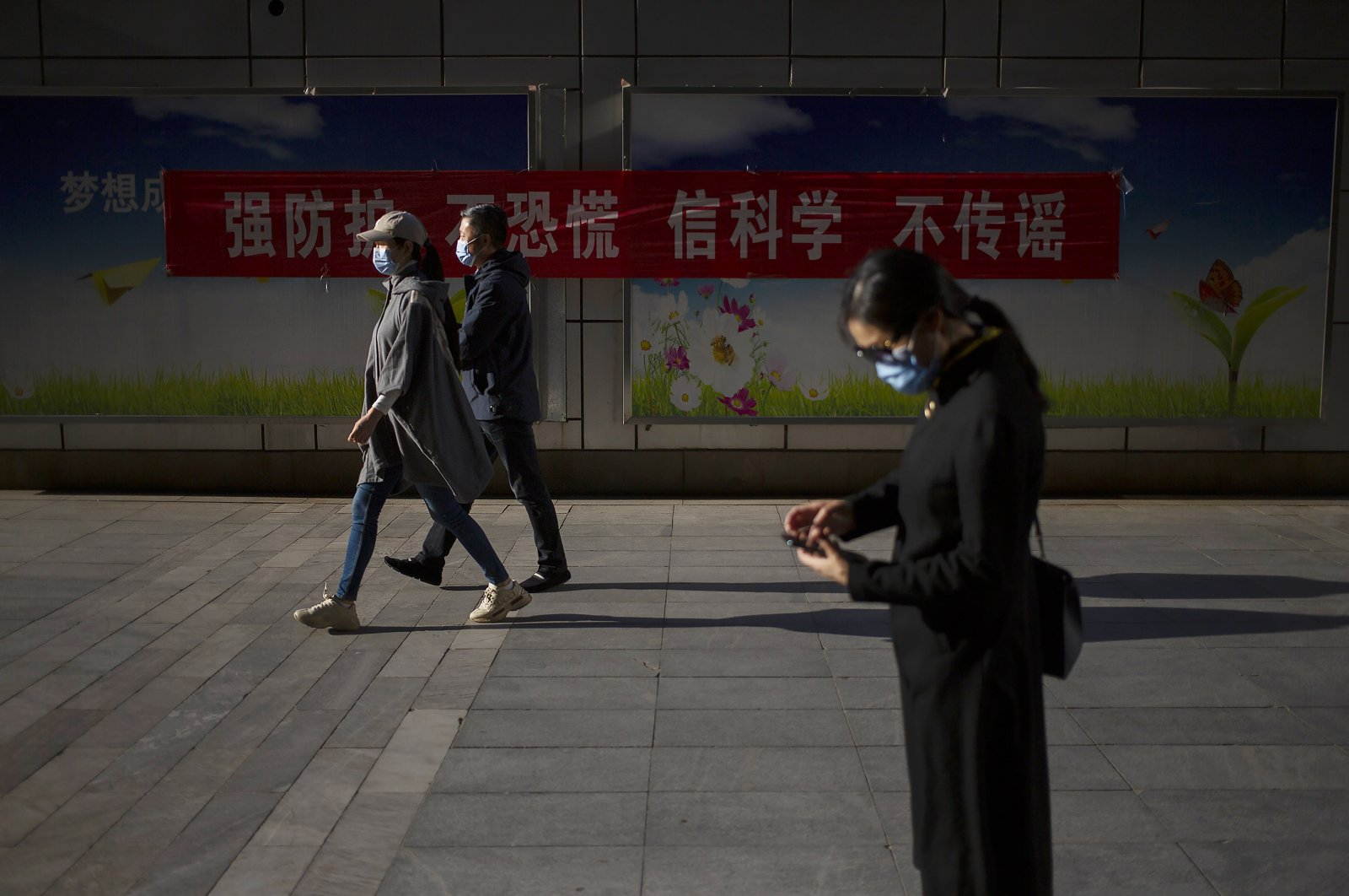 People wear face masks to protect against the spread of the new coronavirus as they walk along a street, Beijing, China, April 23, 2020. (AP Photo)