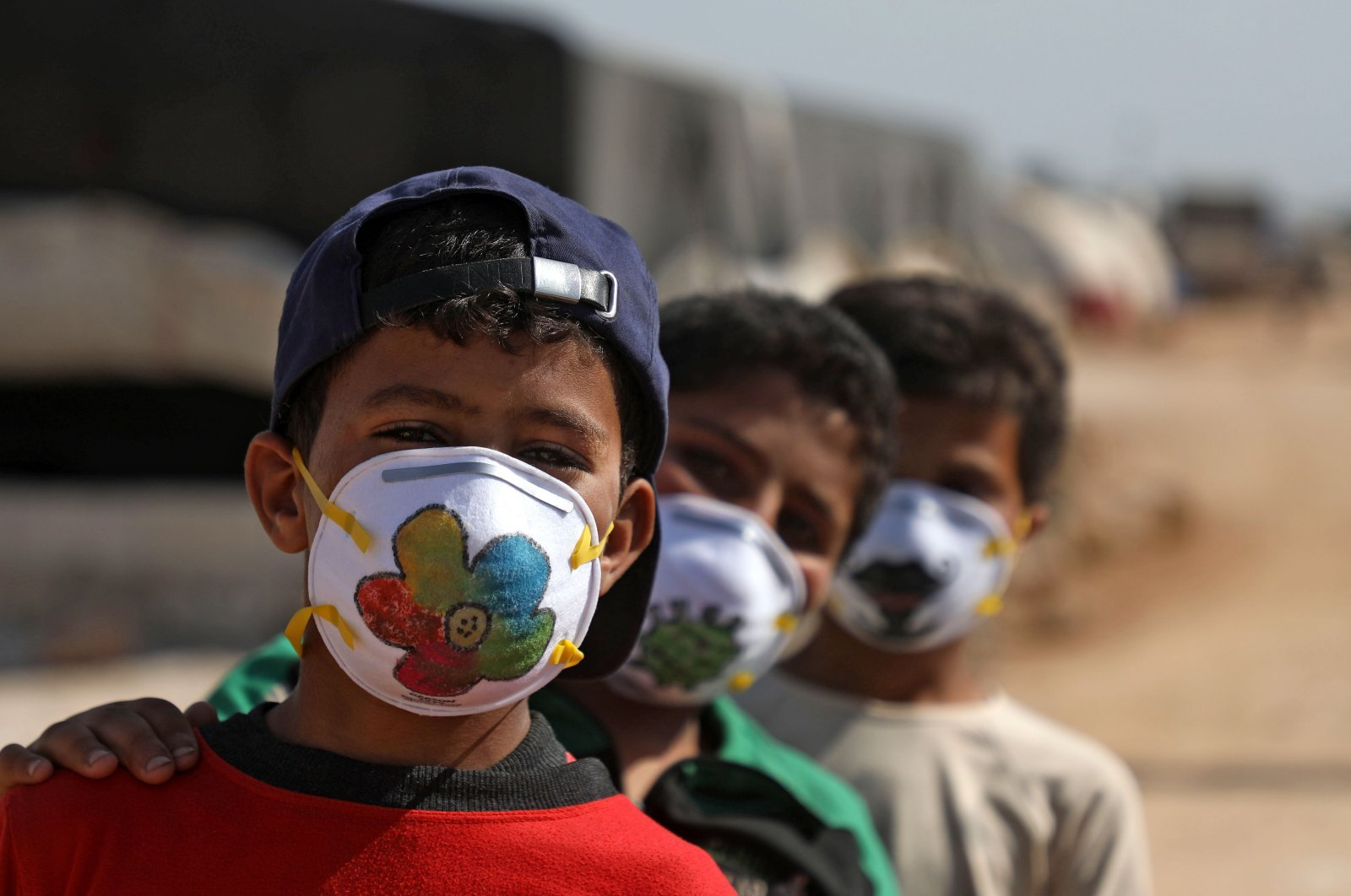 Displaced Syrian boys pose while wearing face masks decorated by artists during a COVID-19 awareness campaign at the Bardaqli camp in the town of Dana in Syria's northwestern Idlib province, on April 20, 2020. (AFP)