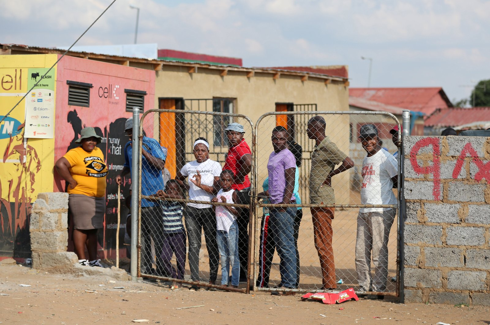 Residents look from behind a closed gate as members of the military patrol during a nationwide lockdown, Soweto, South Africa, April 23, 2020. (REUTERS Photo)