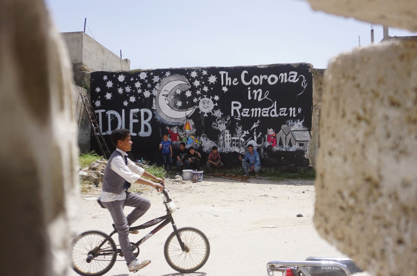 Syrian boys sit in front of a mural by artist Aziz al-Asmar (unseen) depicting the situation of displaced Syrians in camps amid the COVID-19 pandemic ahead of the holy fasting month of Ramadan, in the town of Binnish in Syria's northwestern Idlib province on April 23, 2020. (AFP)