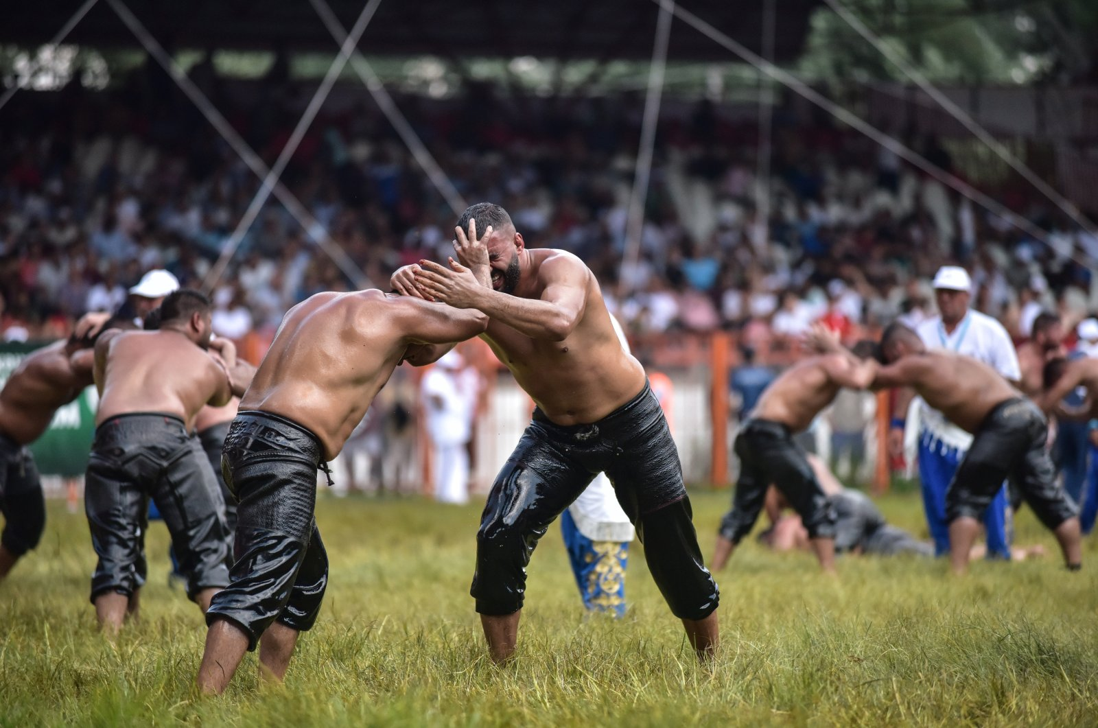 Two oil wrestlers are seen during a match held as part of the 658th Kırkpınar Oil Wrestling tournament at the Sarayiçi wrestling stadium, Edirne, Turkey, July 8, 2019. (DHA Photo).