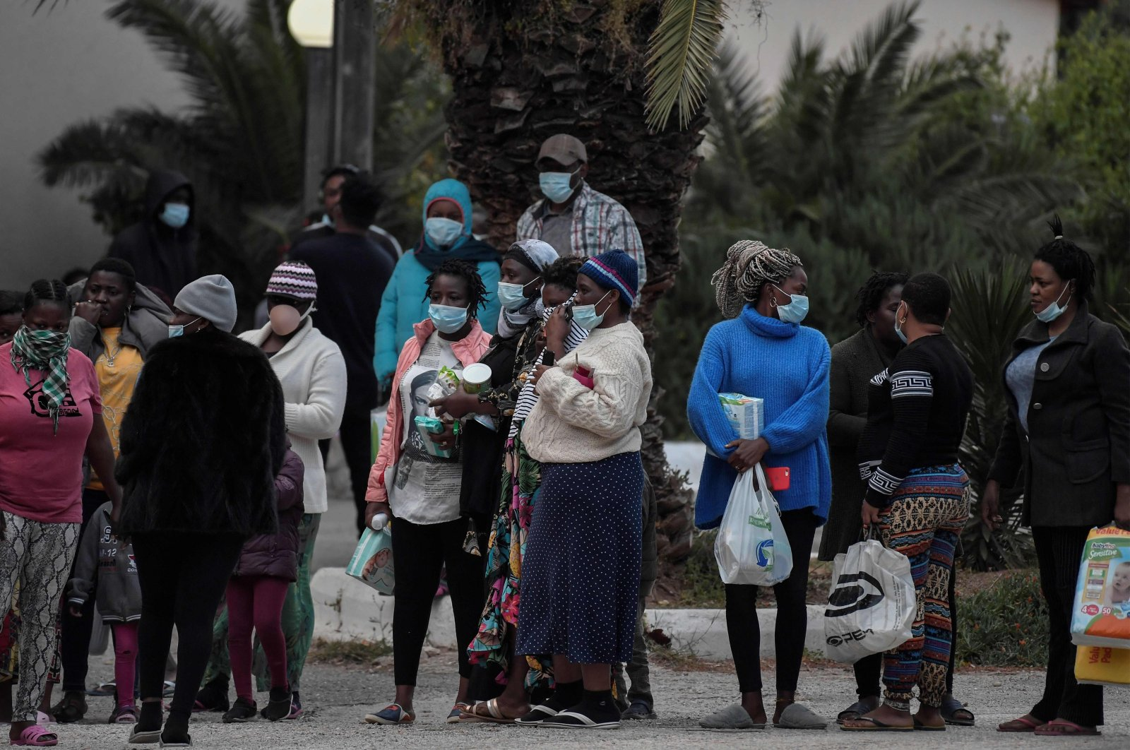 Migrants queue to get necessity items outside a hotel near Kranidi, on April 21, 2020, after some 148 cases of people infected with the COVID-19 were reported among the 470 migrants living there. (AFP Photo)