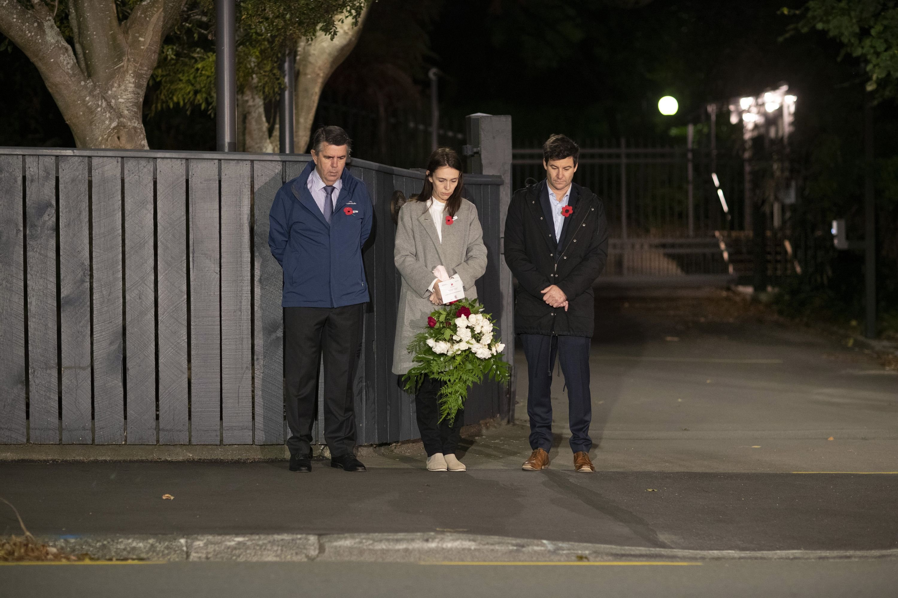 New Zealand Prime Minister Jacinda Ardern (C) with her father Ross Ardern (L) and partner Clarke Gayford stand in respect outside premier house in remembrance of ANZAC in Wellington on April 25, 2020. (AFP Photo)