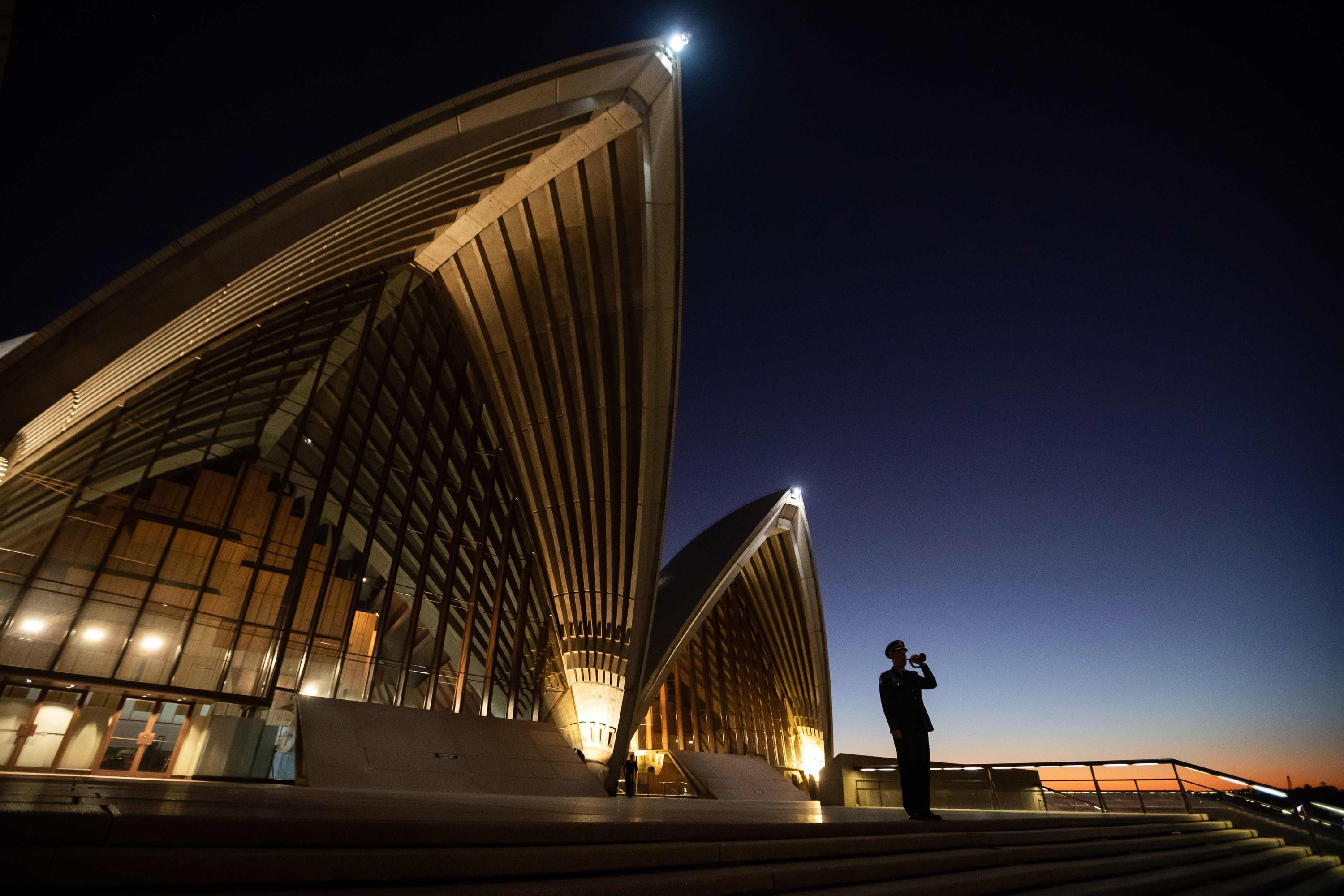 This handout picture taken and released on April 25, 2020 by the Sydney Opera House shows a lone bugler playing The Last Post on the steps of the Sydney Opera House. (Photo by Daniel BOUD / Sydney Opera House / AFP)