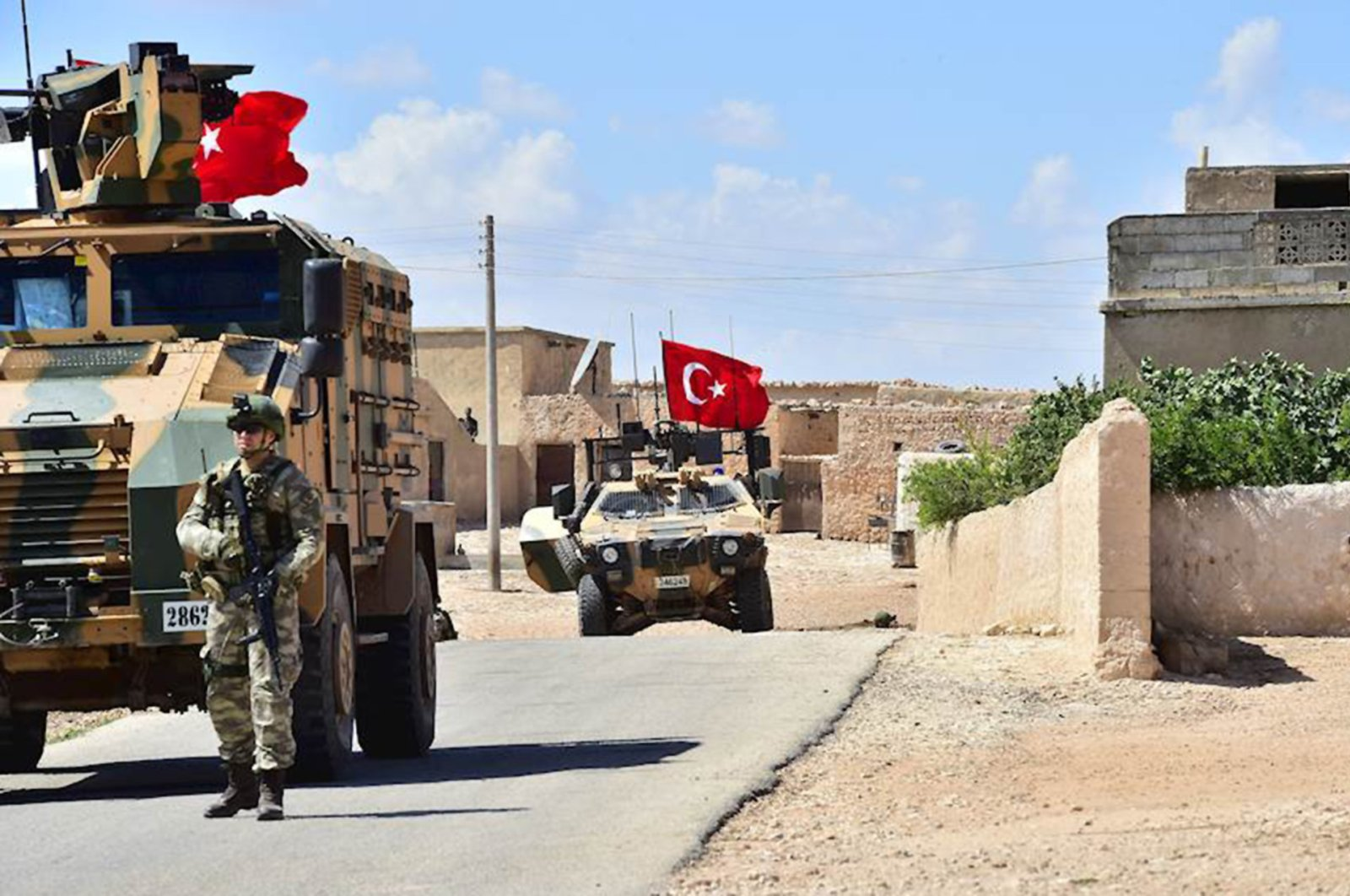A handout picture realeased by the Turkish Armed Forces shows Turkish soldiers accompanied by armoured vehicles patrolling between the city of Manbij in northern Syria and an area it controls after a 2016-2017 military incursion on June 18, 2018.  (AFP Photo)